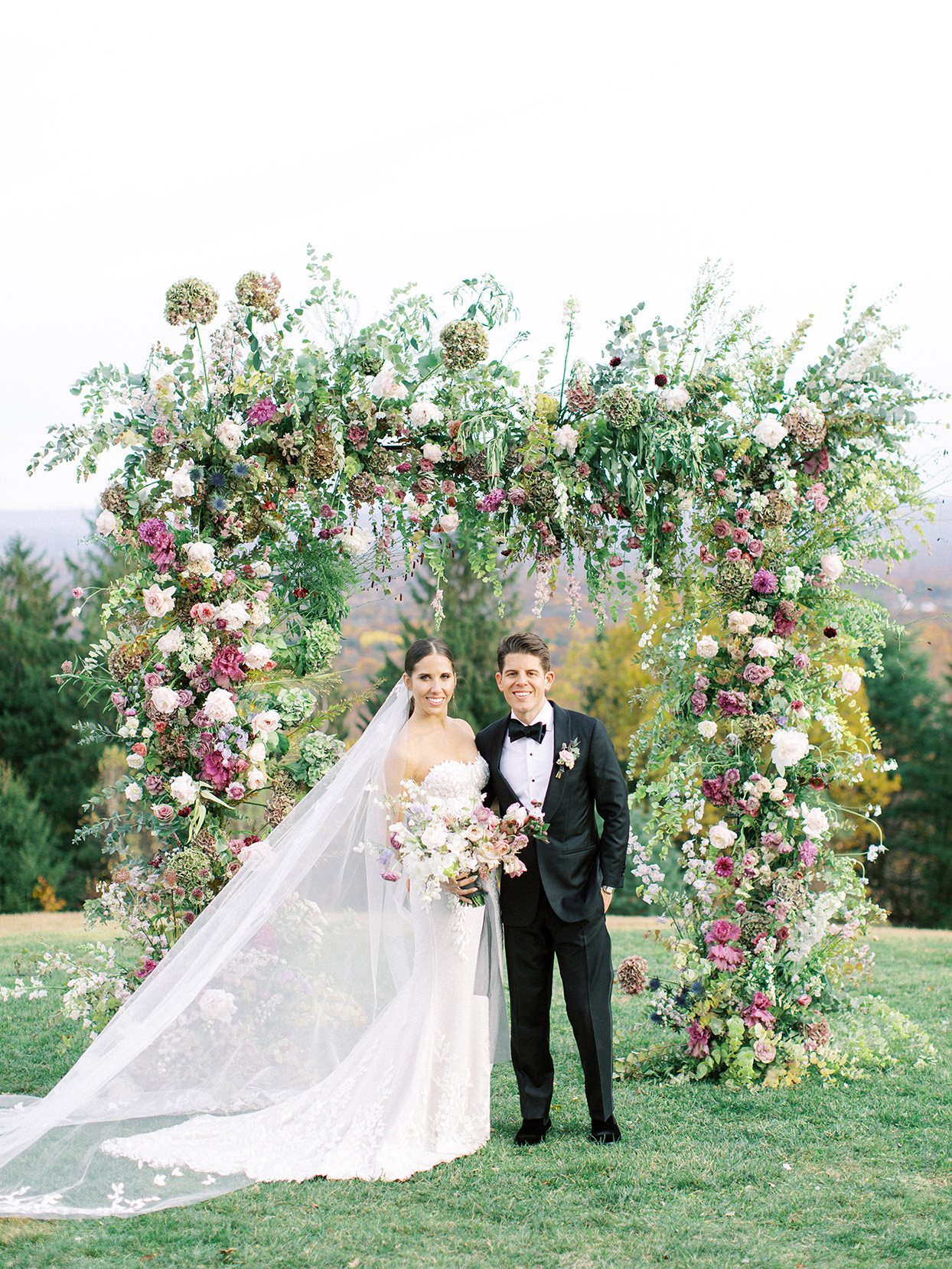 elizabeth nicholas wedding couple portrait in front of floral arch