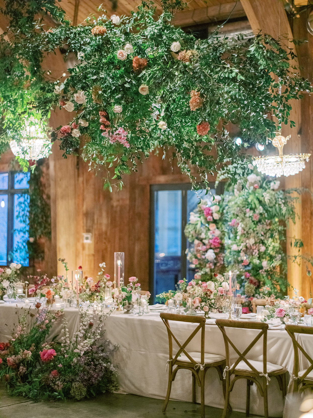 wedding reception long table with floral centerpiece, floor arrangements, and hanging installment