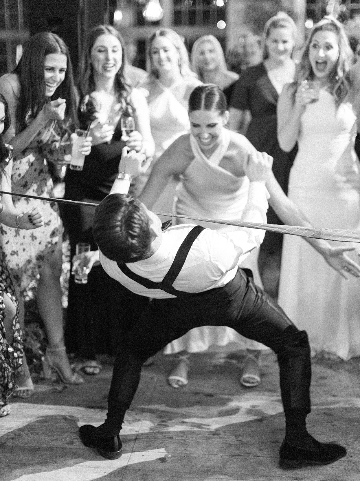 groom doing limbo under tie with bride laughs