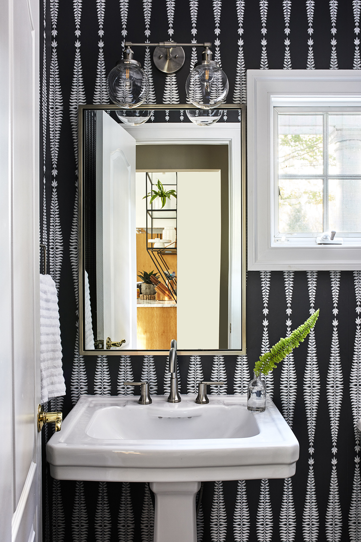 black patterned wallpaper in powder room with mirror and white sink