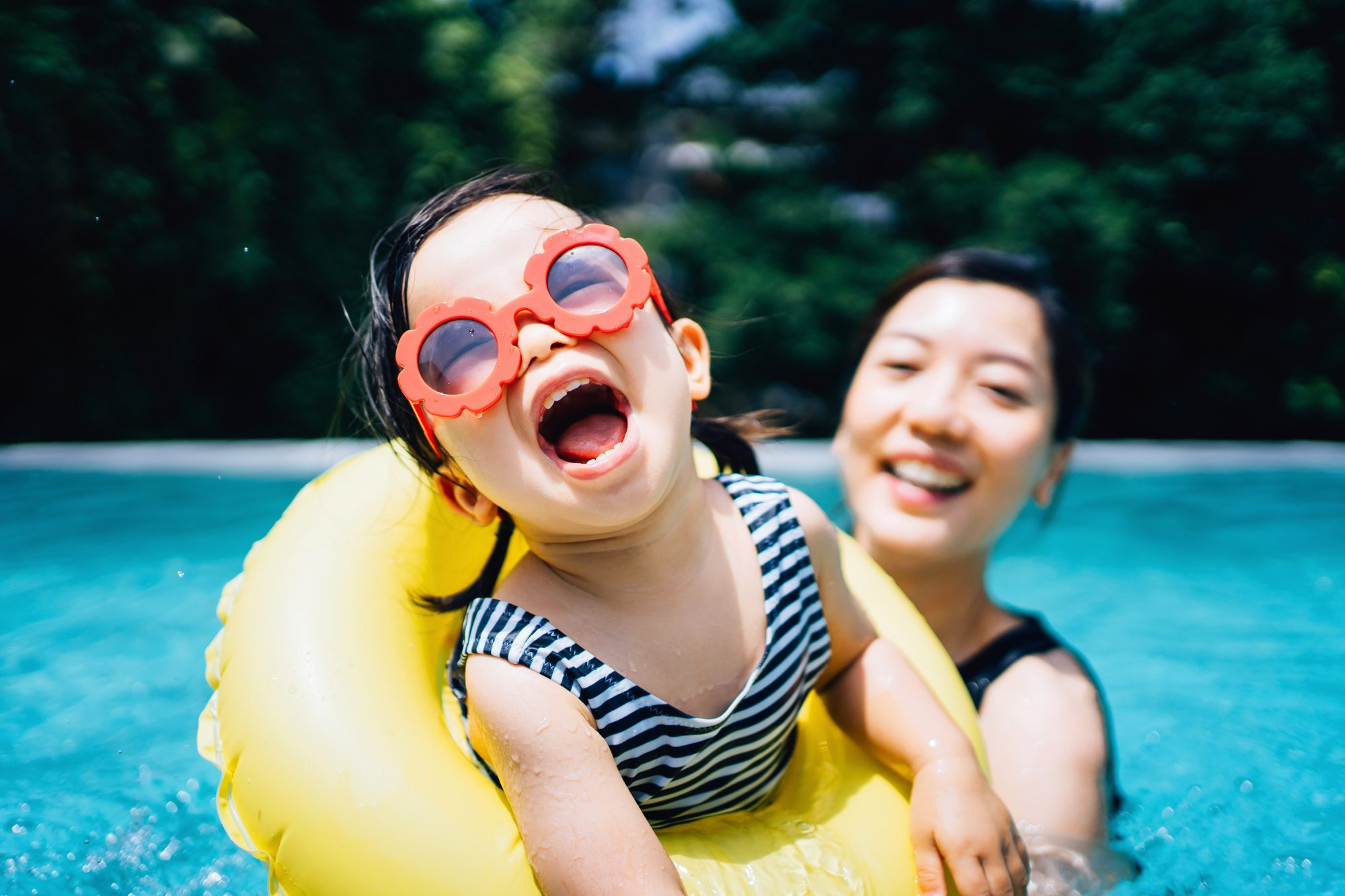 asian toddler swimming with mom