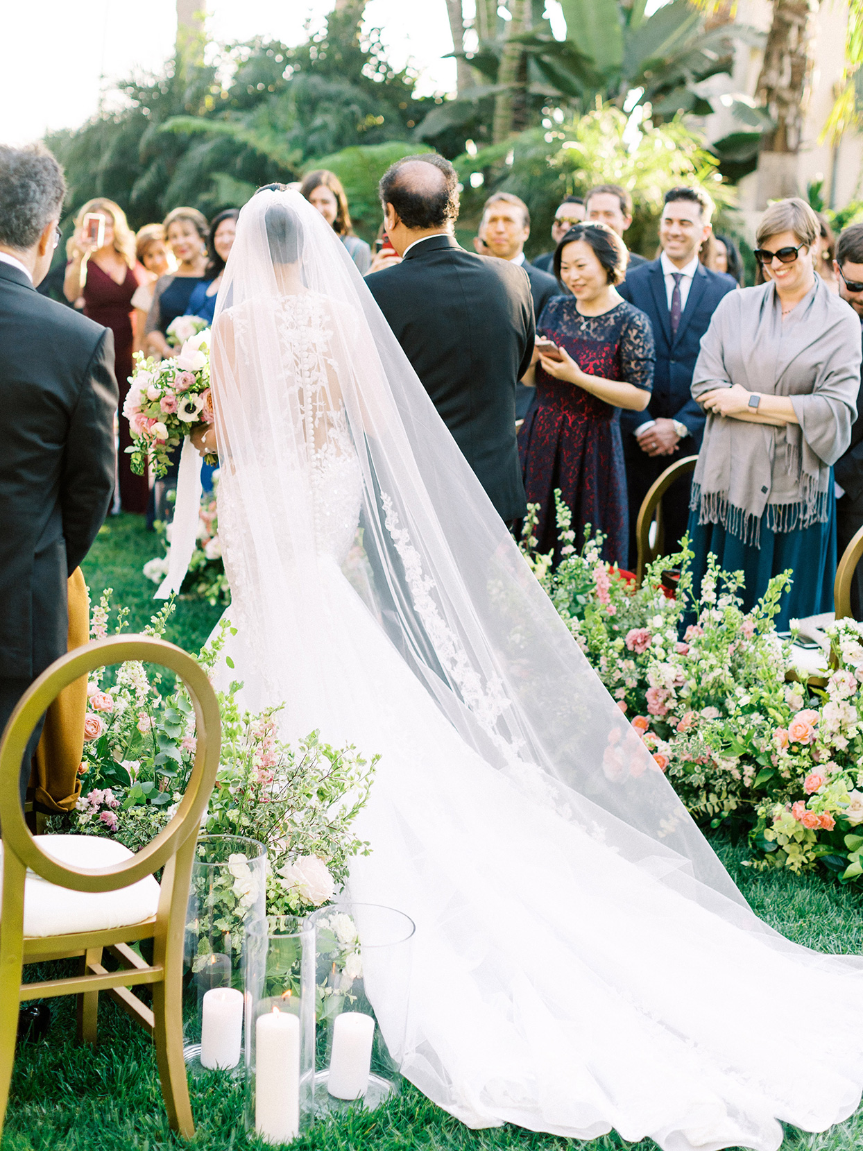 bride processing down aisle with father while guests stand and watch
