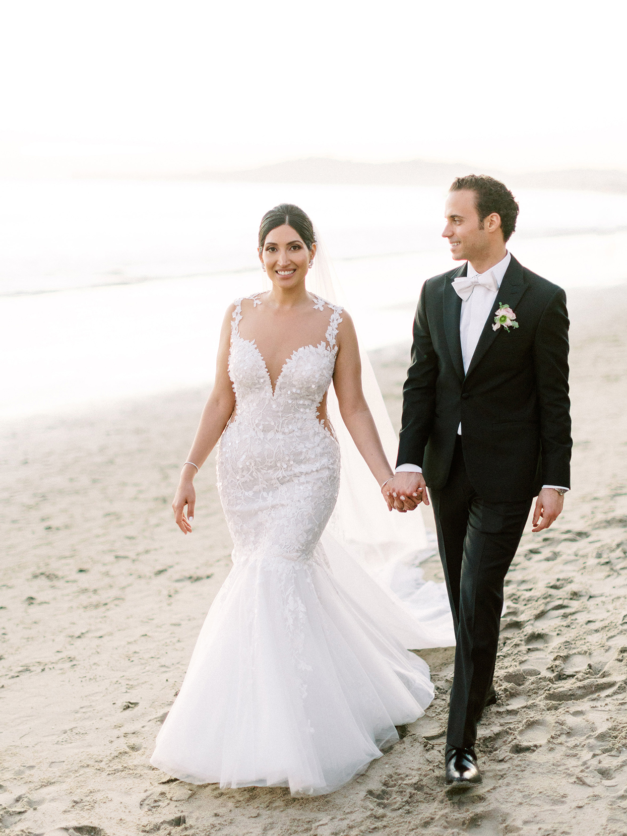 wedding couple walking along beach for portraits