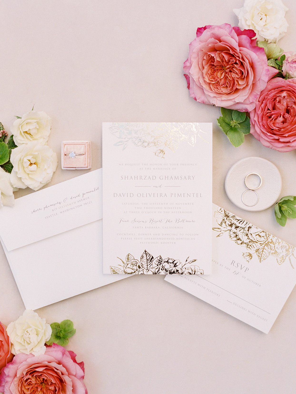 white wedding invites with shiny gold and silver decoration and pink flowers