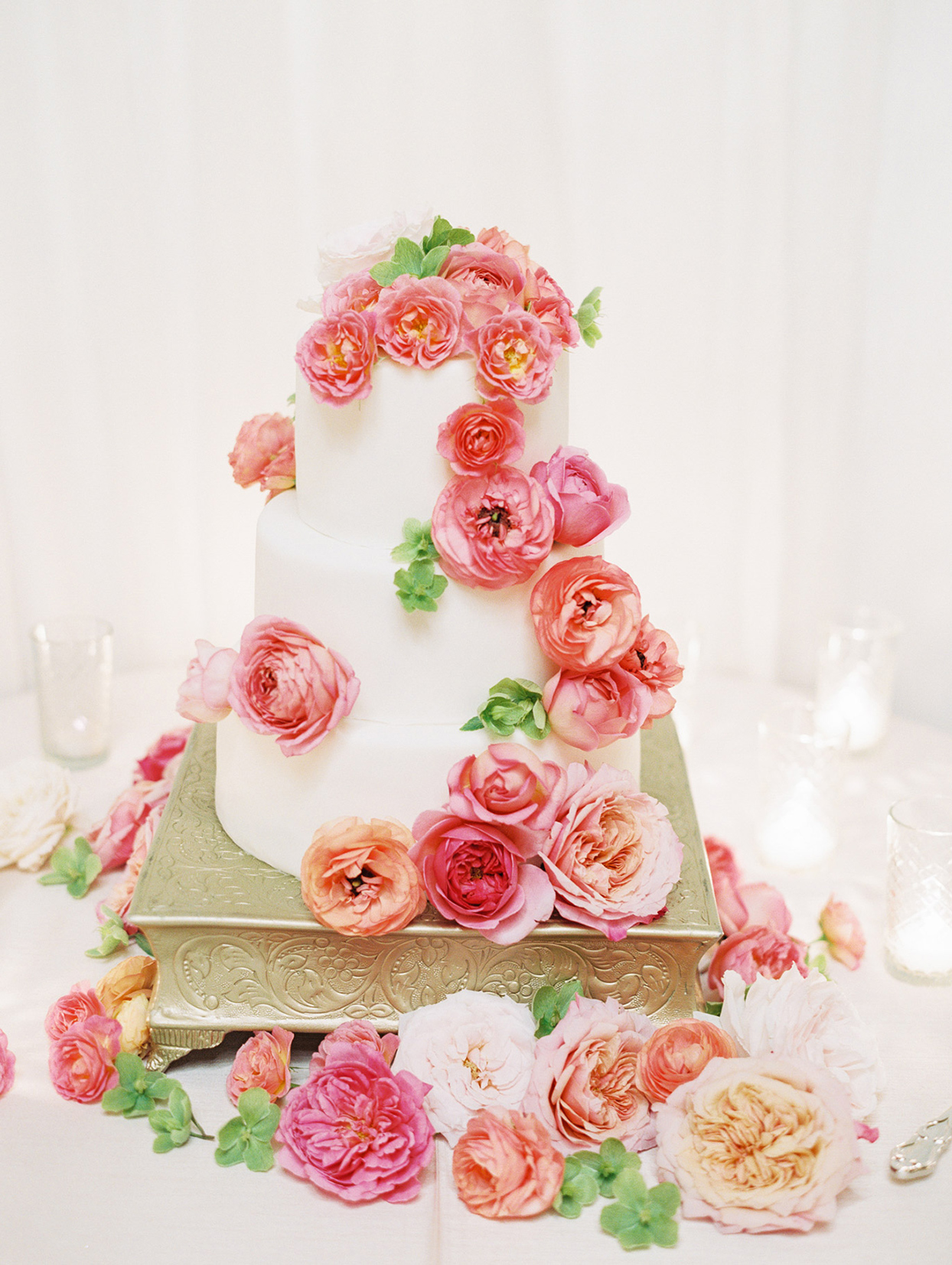 white wedding cake on gold stand with pink and peach flowers