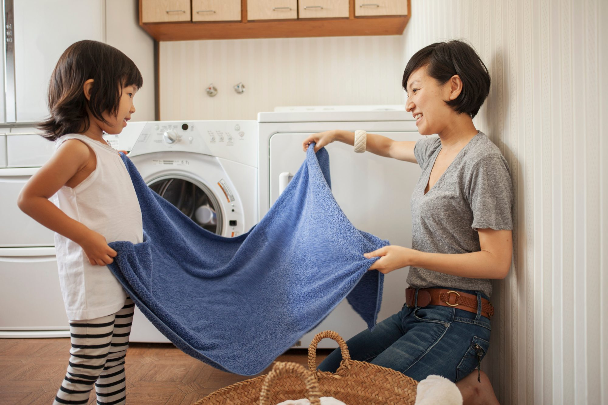 mother daughter folding towel