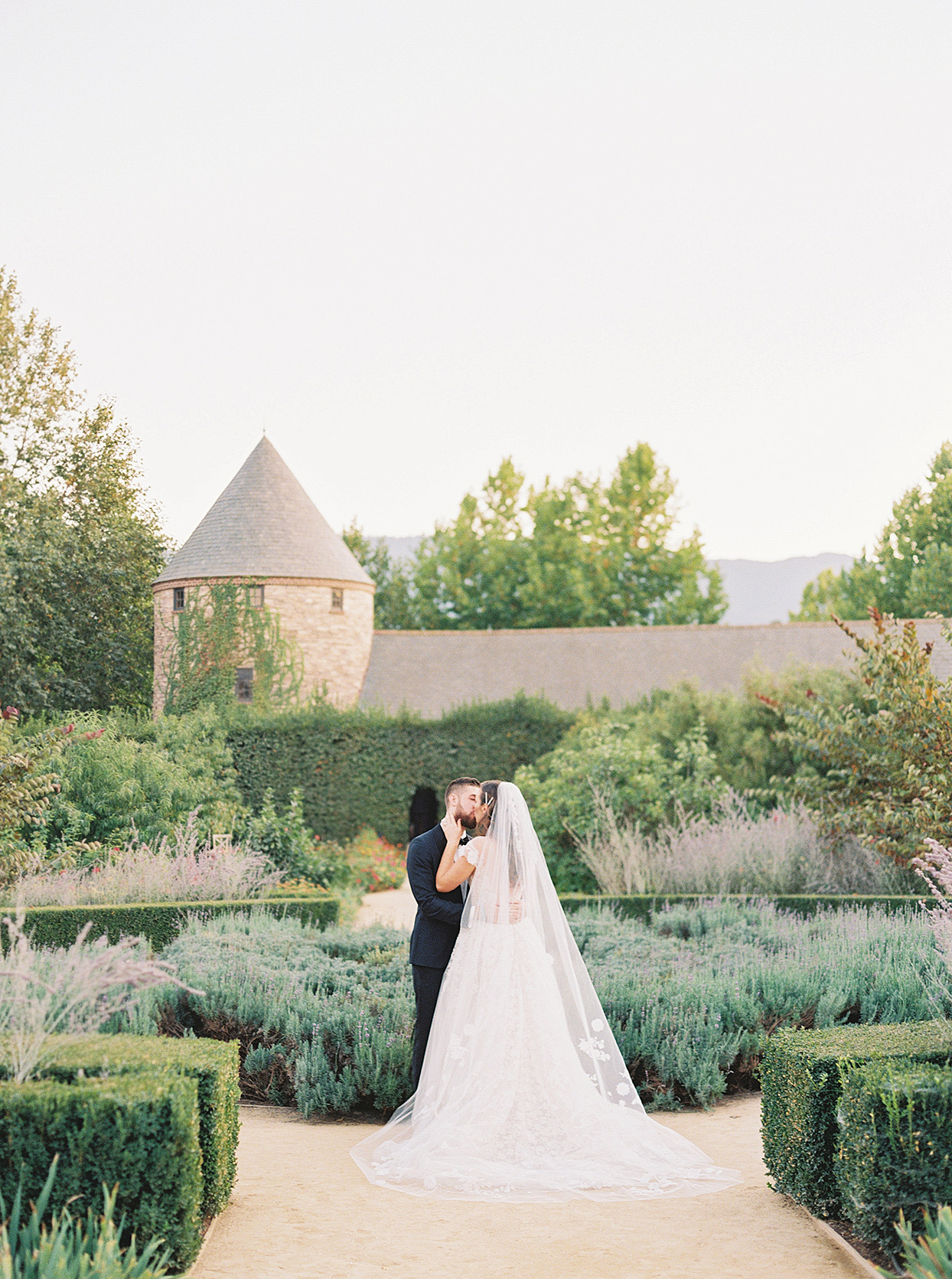 sam kyler wedding couple kissing in garden at venue