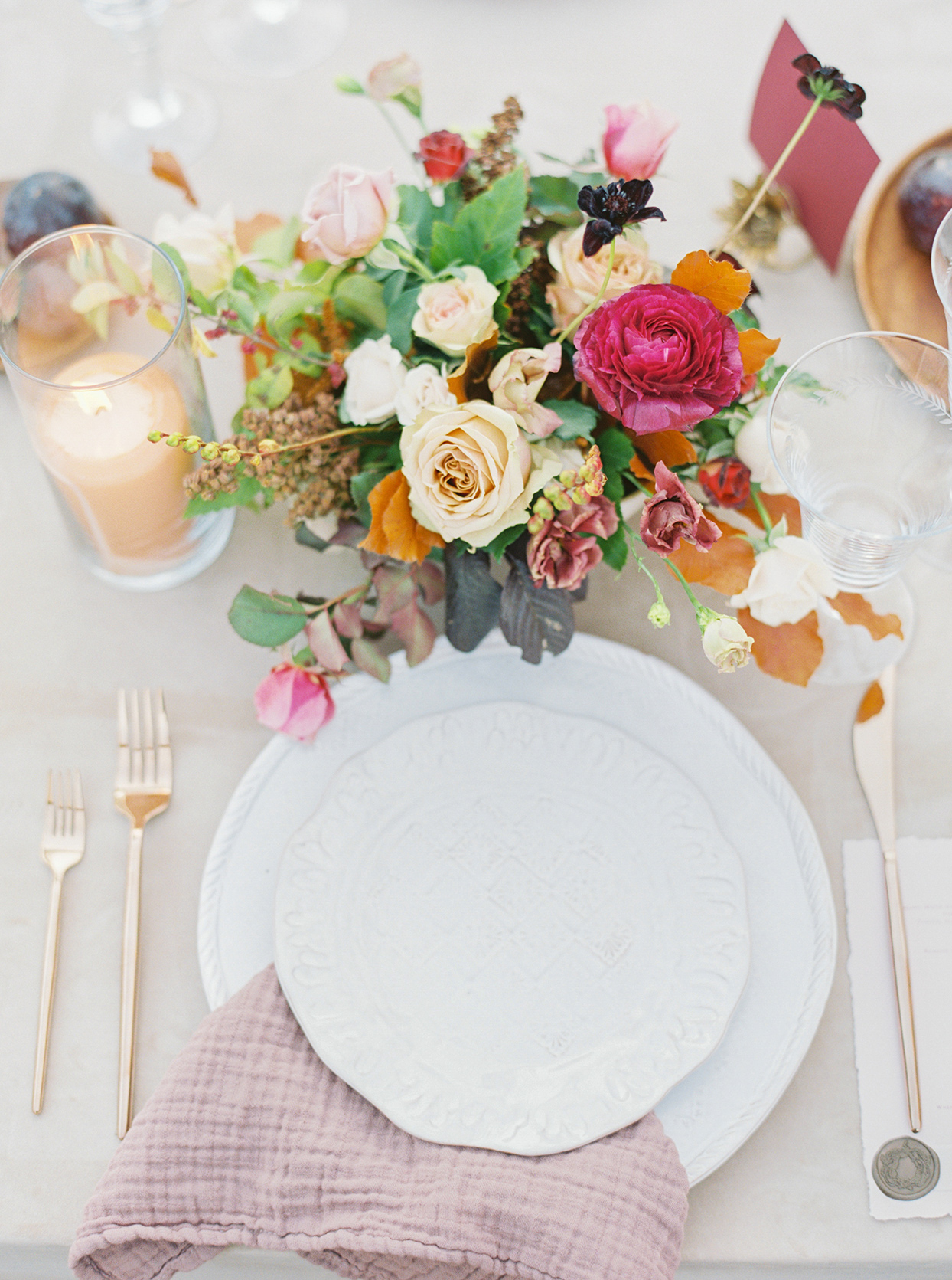 wedding reception white place setting with colorful fall floral bouquet