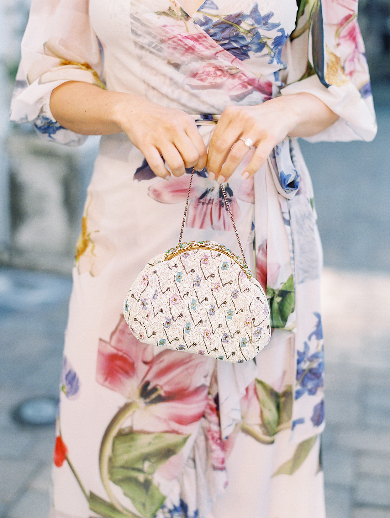 bride in floral rehearsal dinner dress holding beaded purse