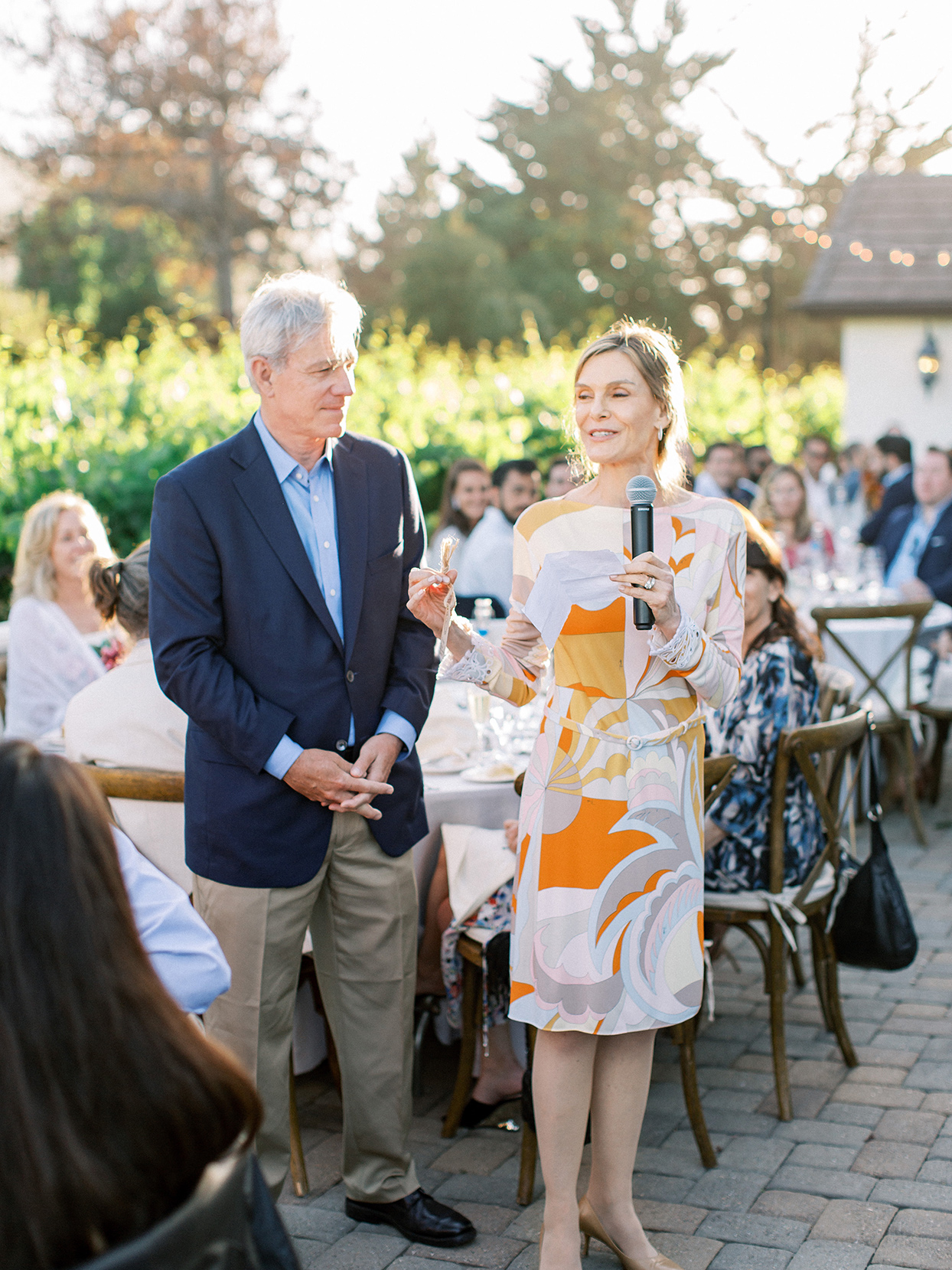 parents giving speech at outdoor rehearsal dinner