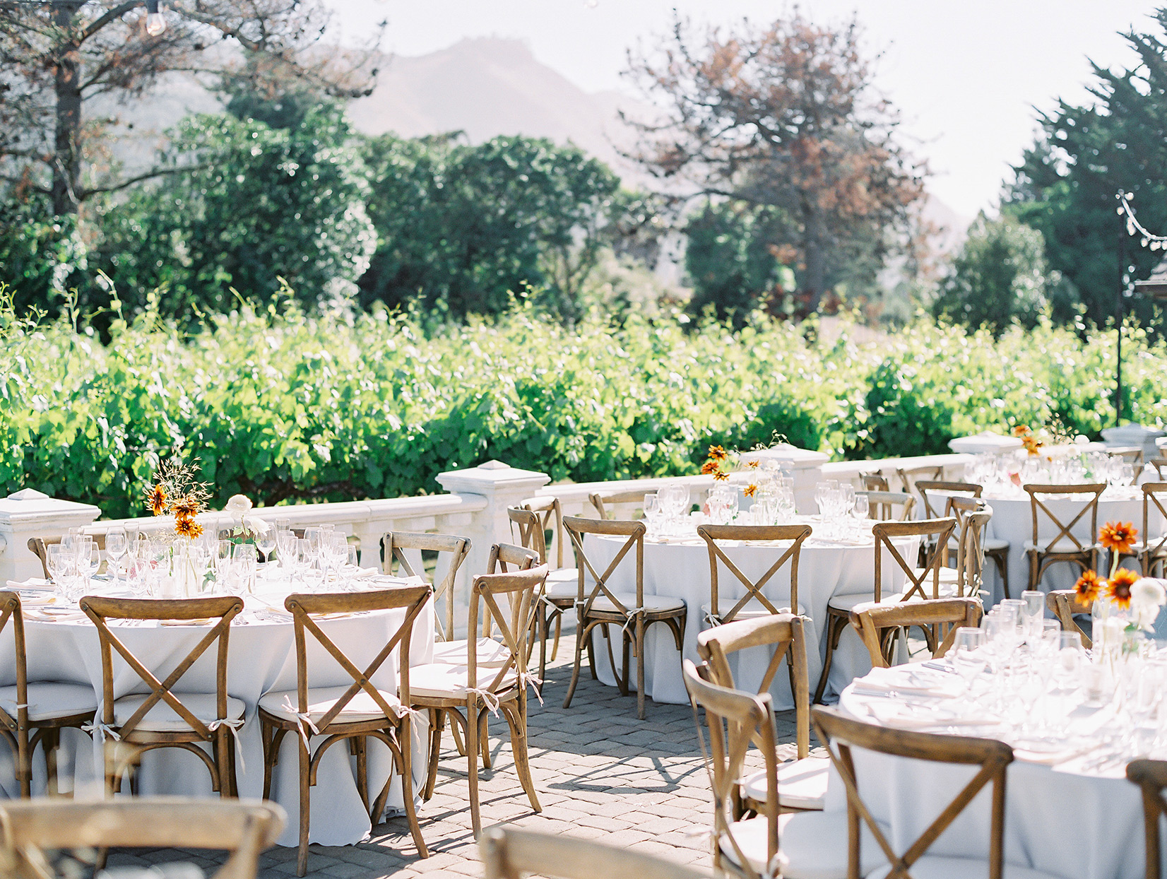 white tables with wooden chairs set up on patio