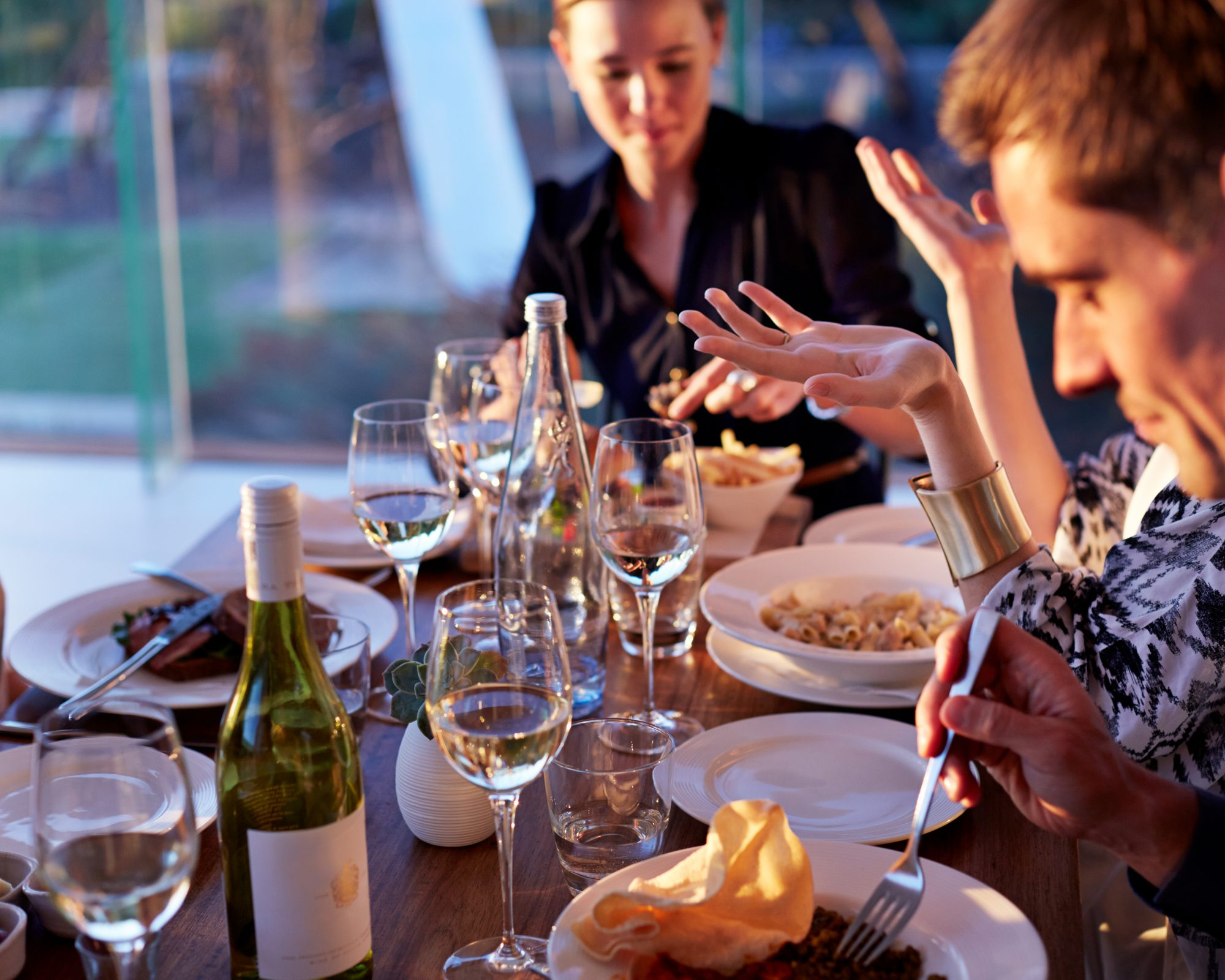 people at dinner table with food, wine bottles, and glasses