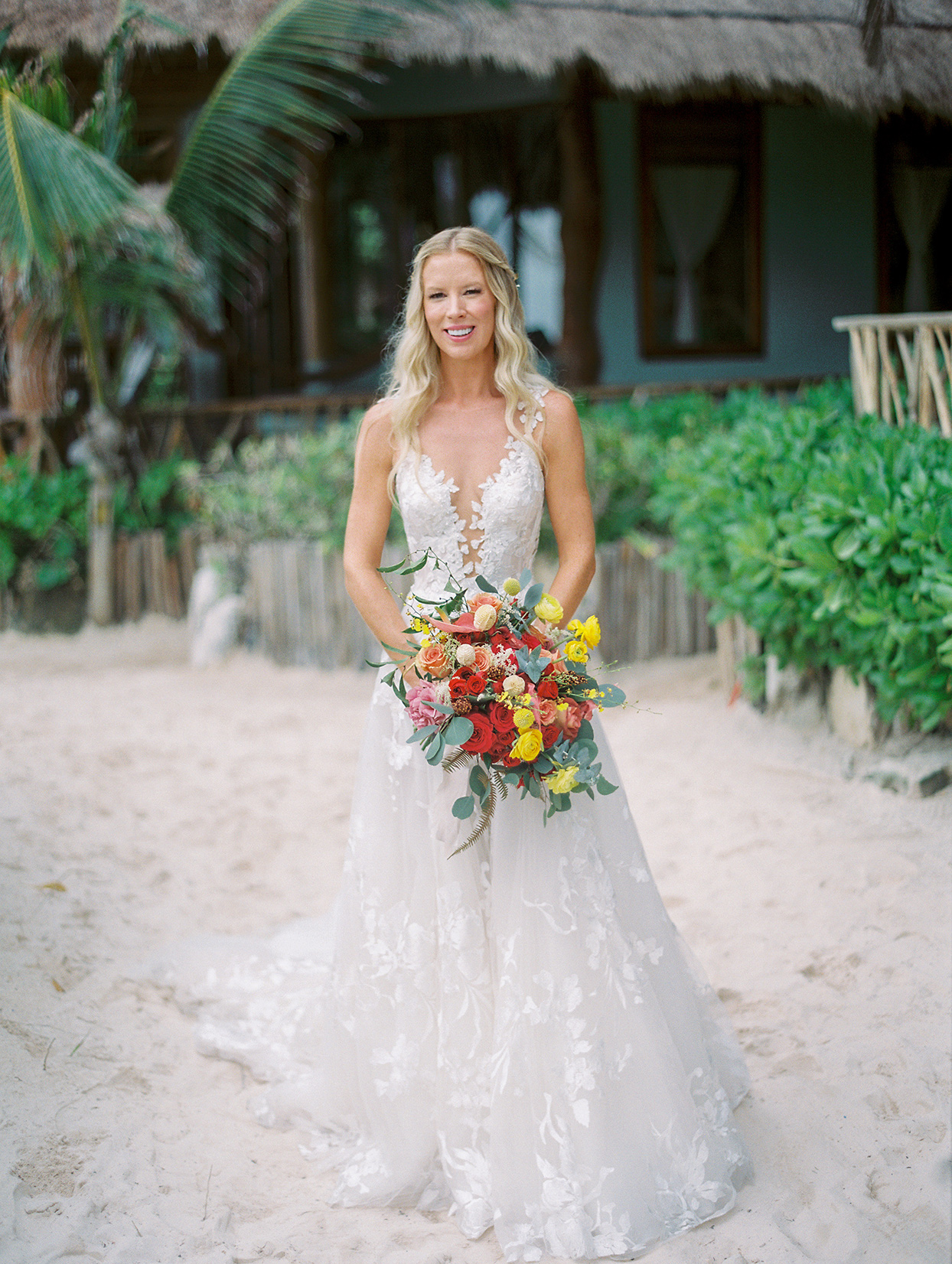bride in sheer overlay white dress holding yellow and red wedding bouquet