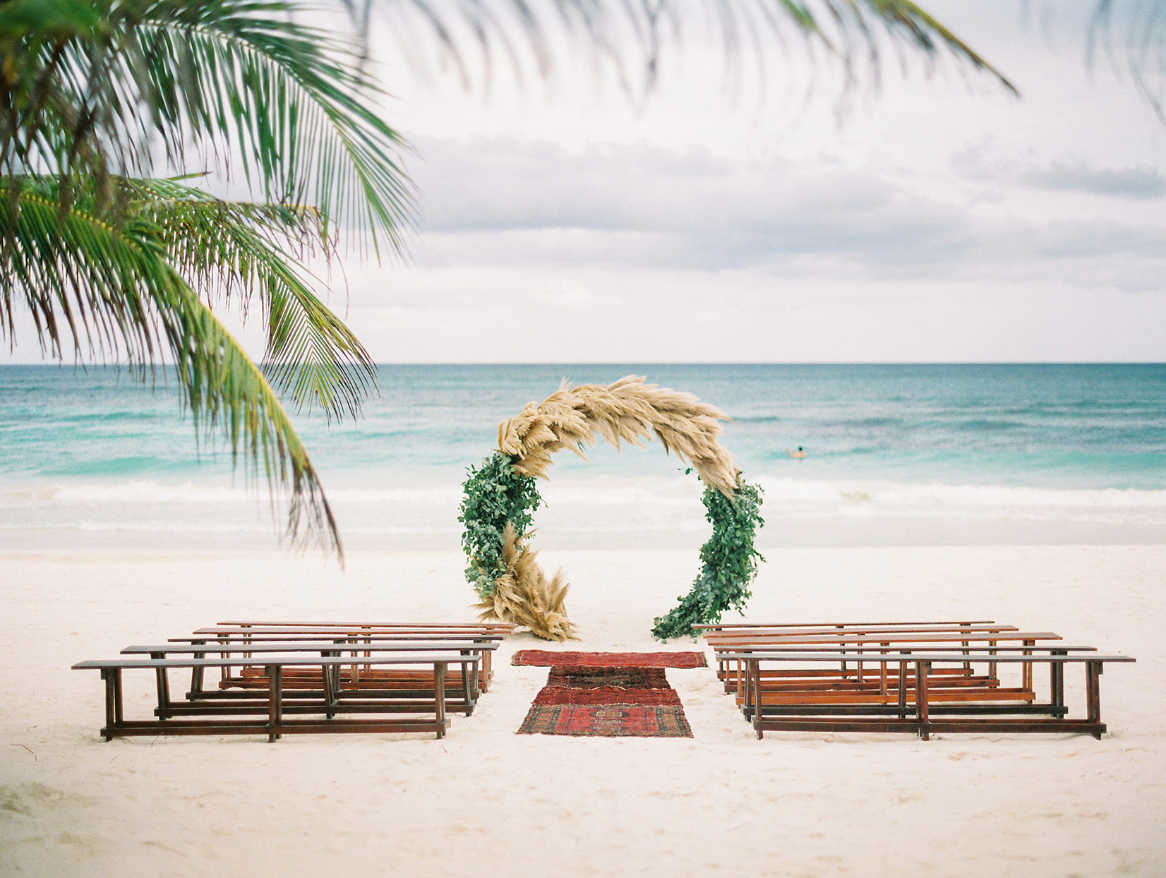 wedding ceremony wooden benches and circular arch set up on the beach