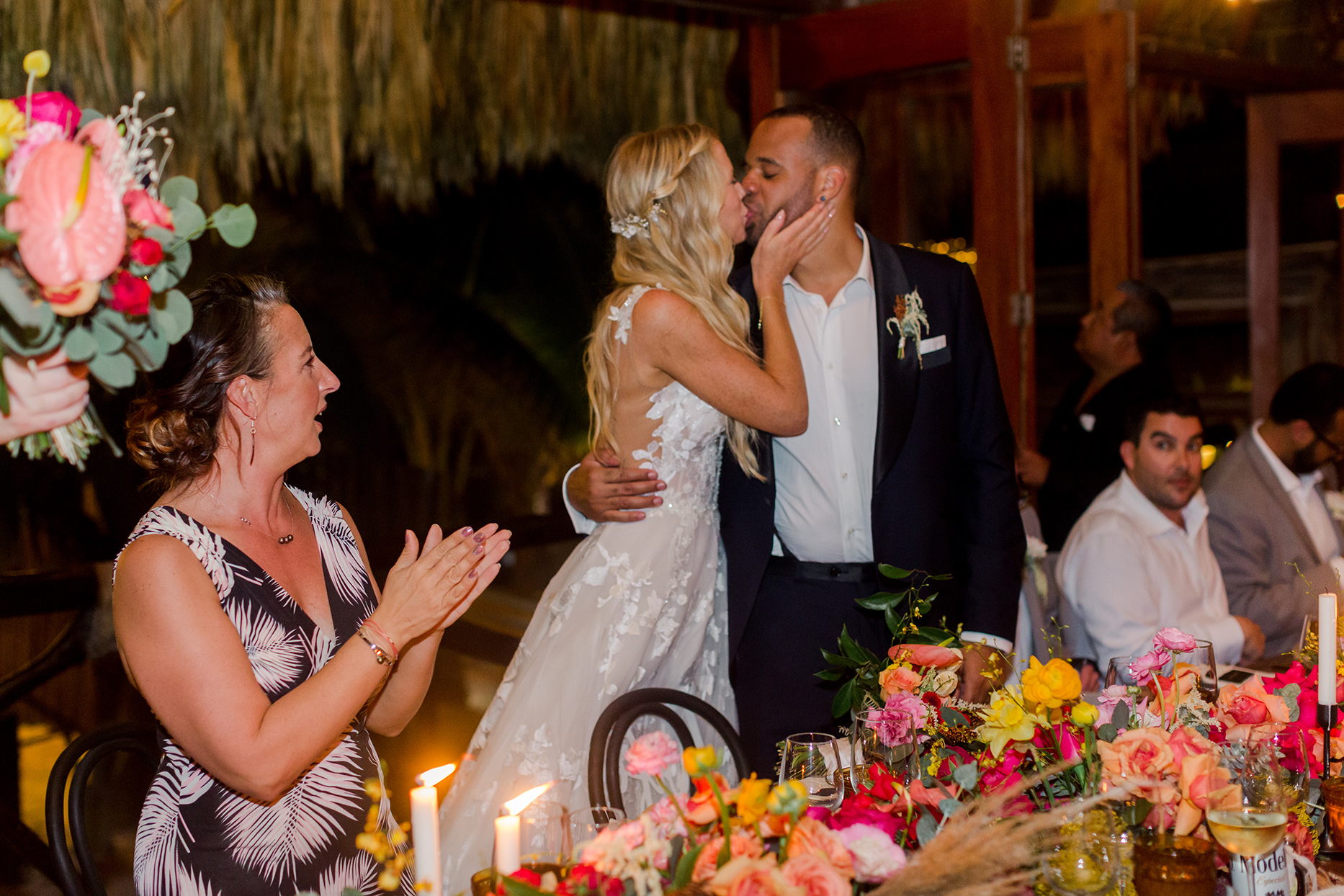 wedding couple kissing during reception in front of colorful table