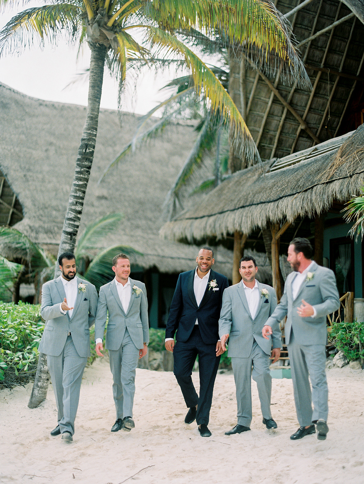 groom and groomsmen in light colored suits walking on beach