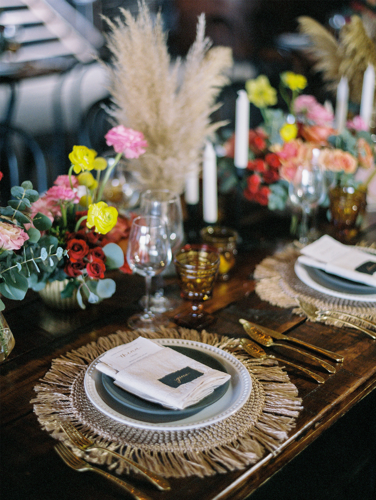 bohemian place setting with gold silverware and colorful floral centerpieces