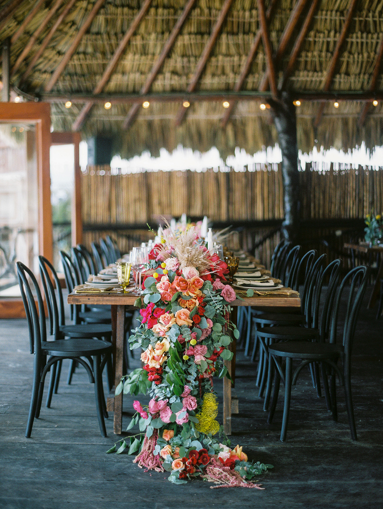 elegant long wedding table with black chairs and sweeping garland of colorful flowers