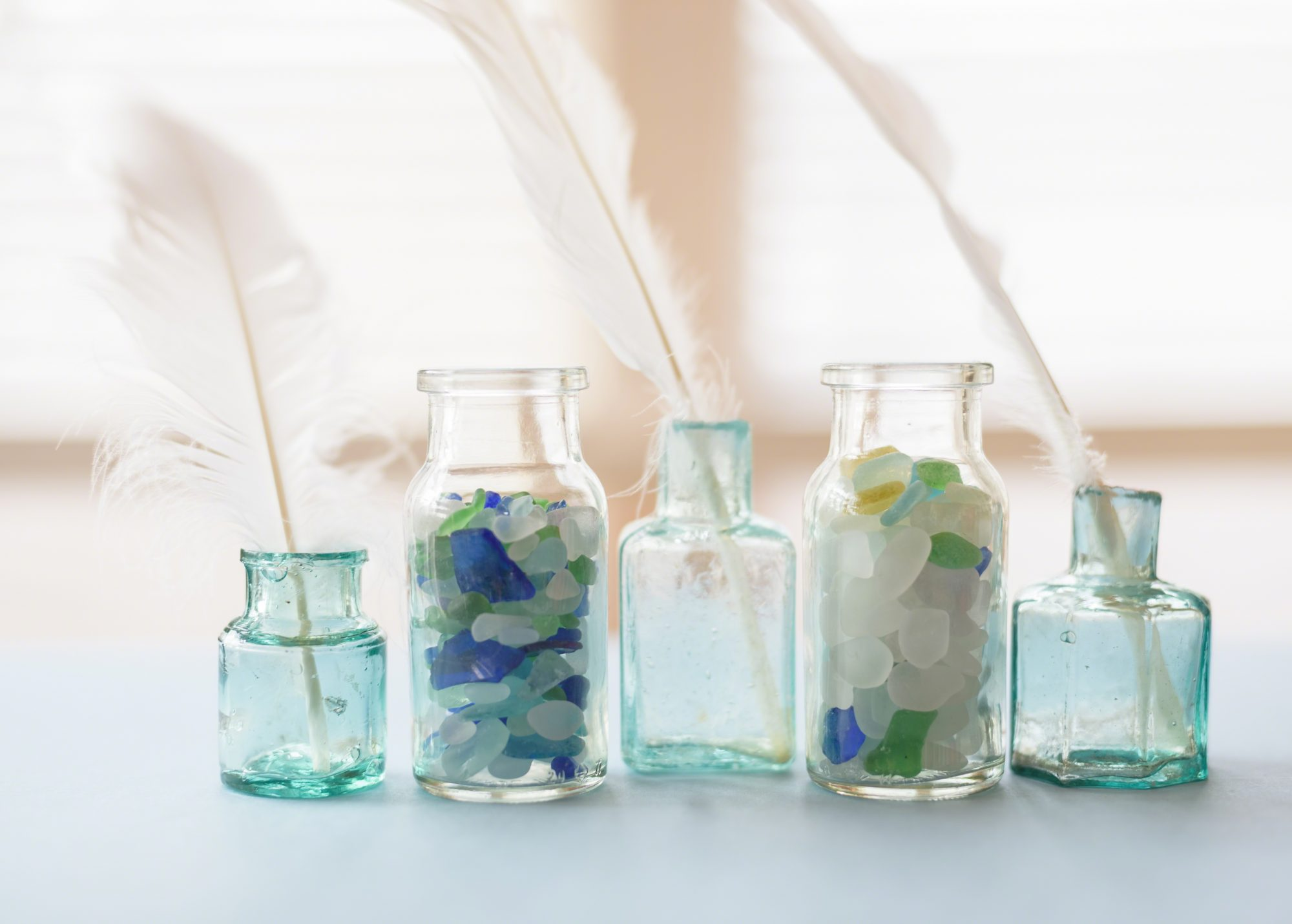 tiny blue glass jars filled with sea glass and white feathers