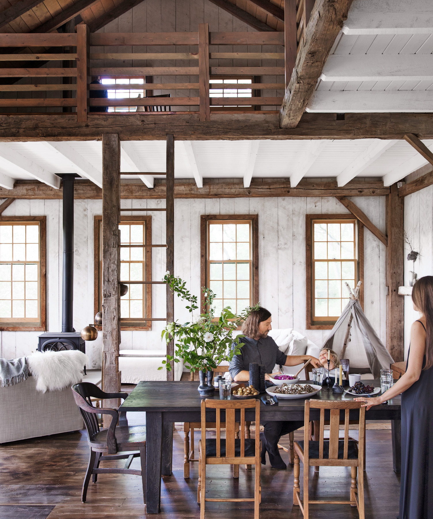 rustic dining room with ladder to loft above