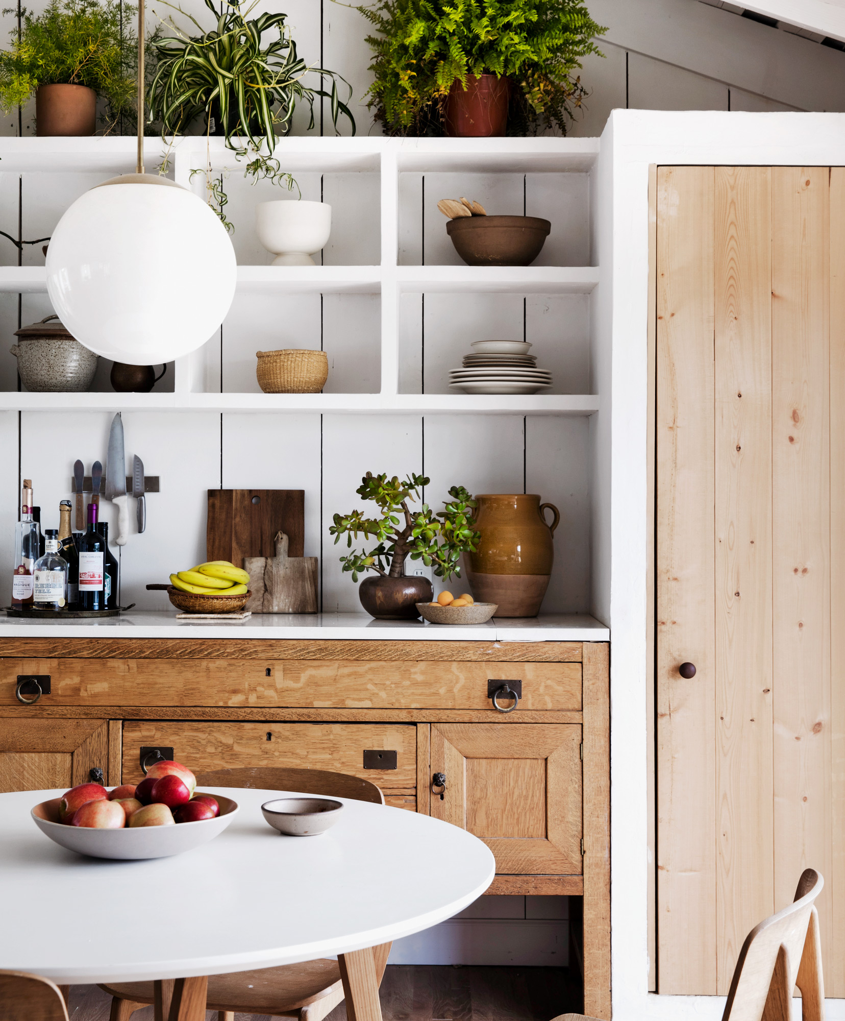 eating nook with white open shelves white round table