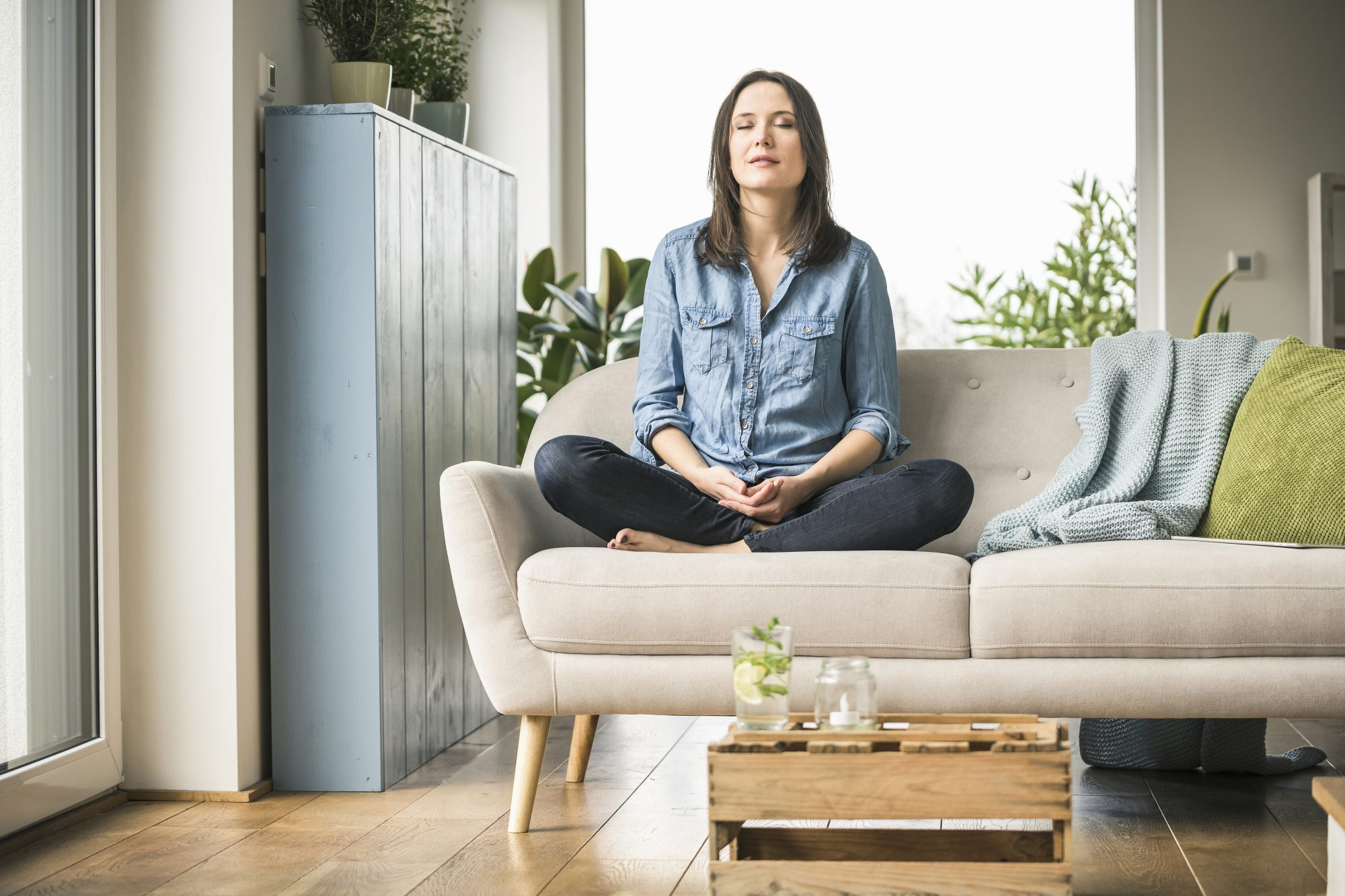 woman meditating on couch