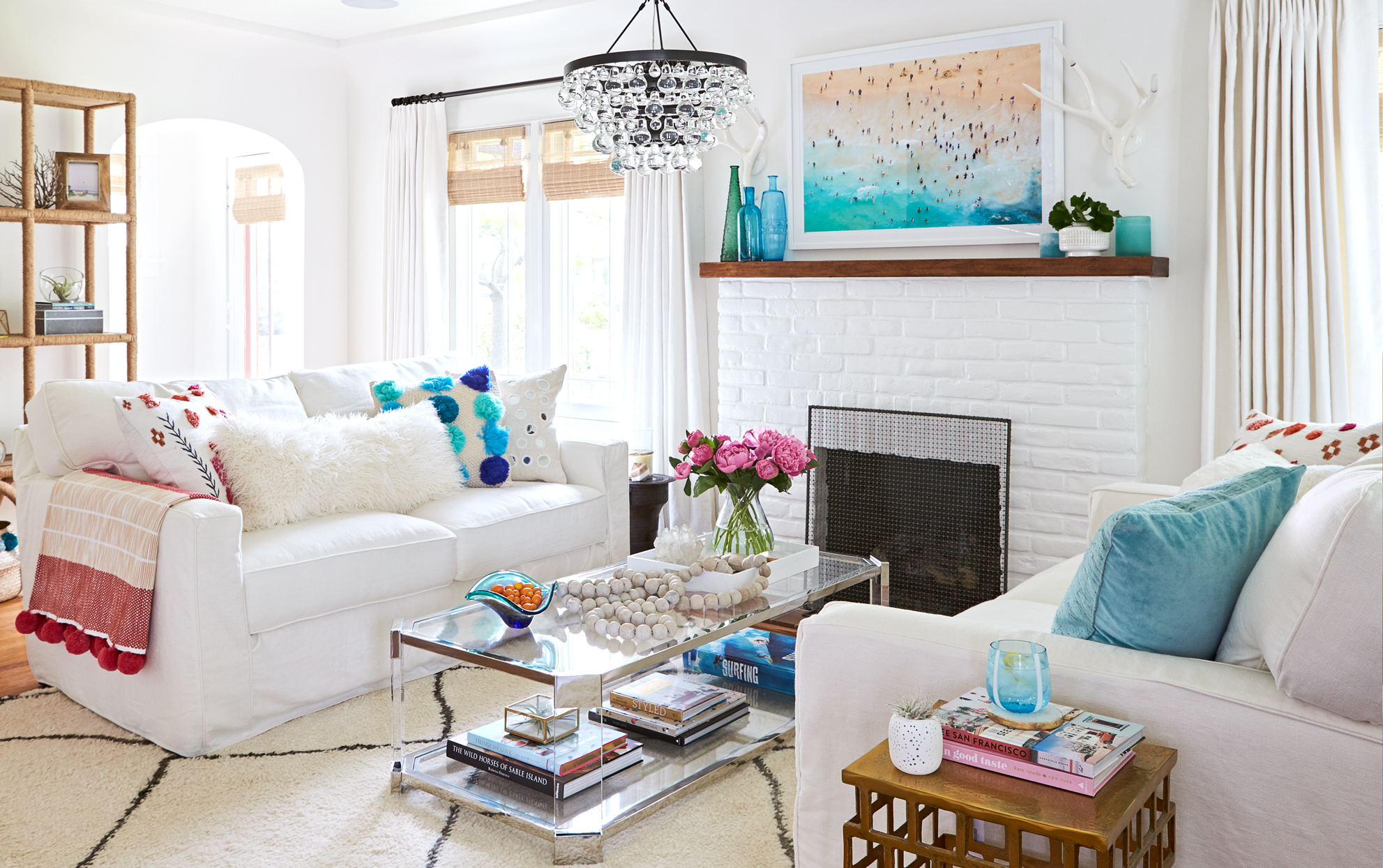 A coastal-style living room with bright white furniture and turquoise accents.