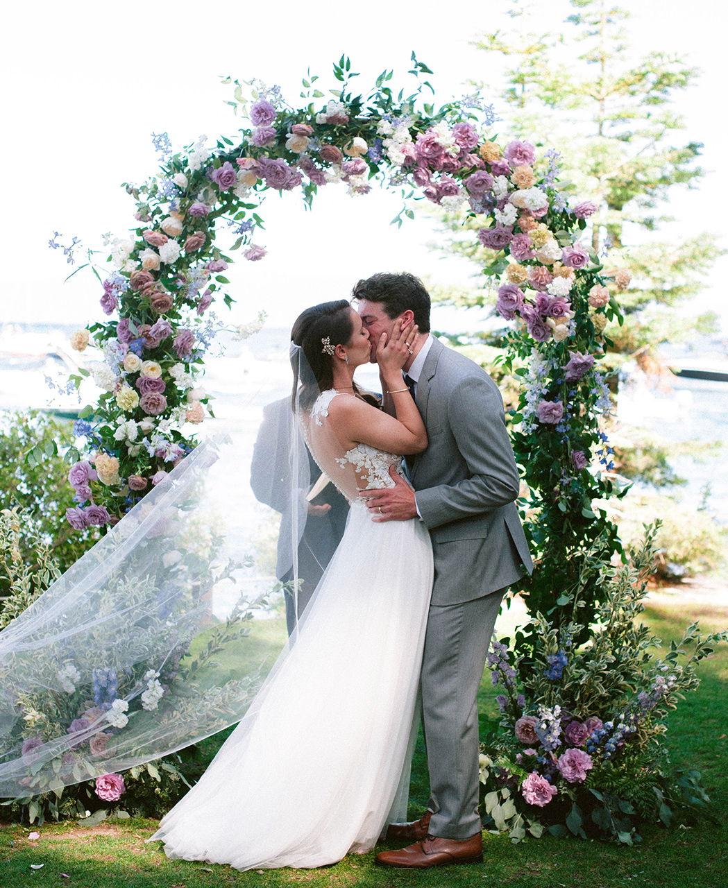 wedding couple kiss under floral arch lake view
