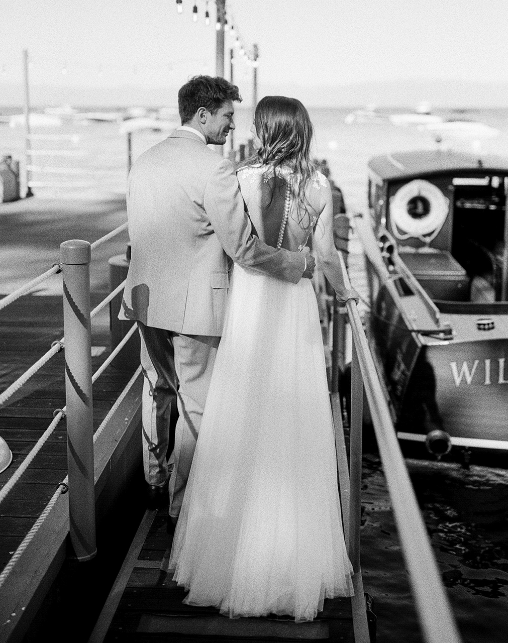 wedding couple walking along pier with boat