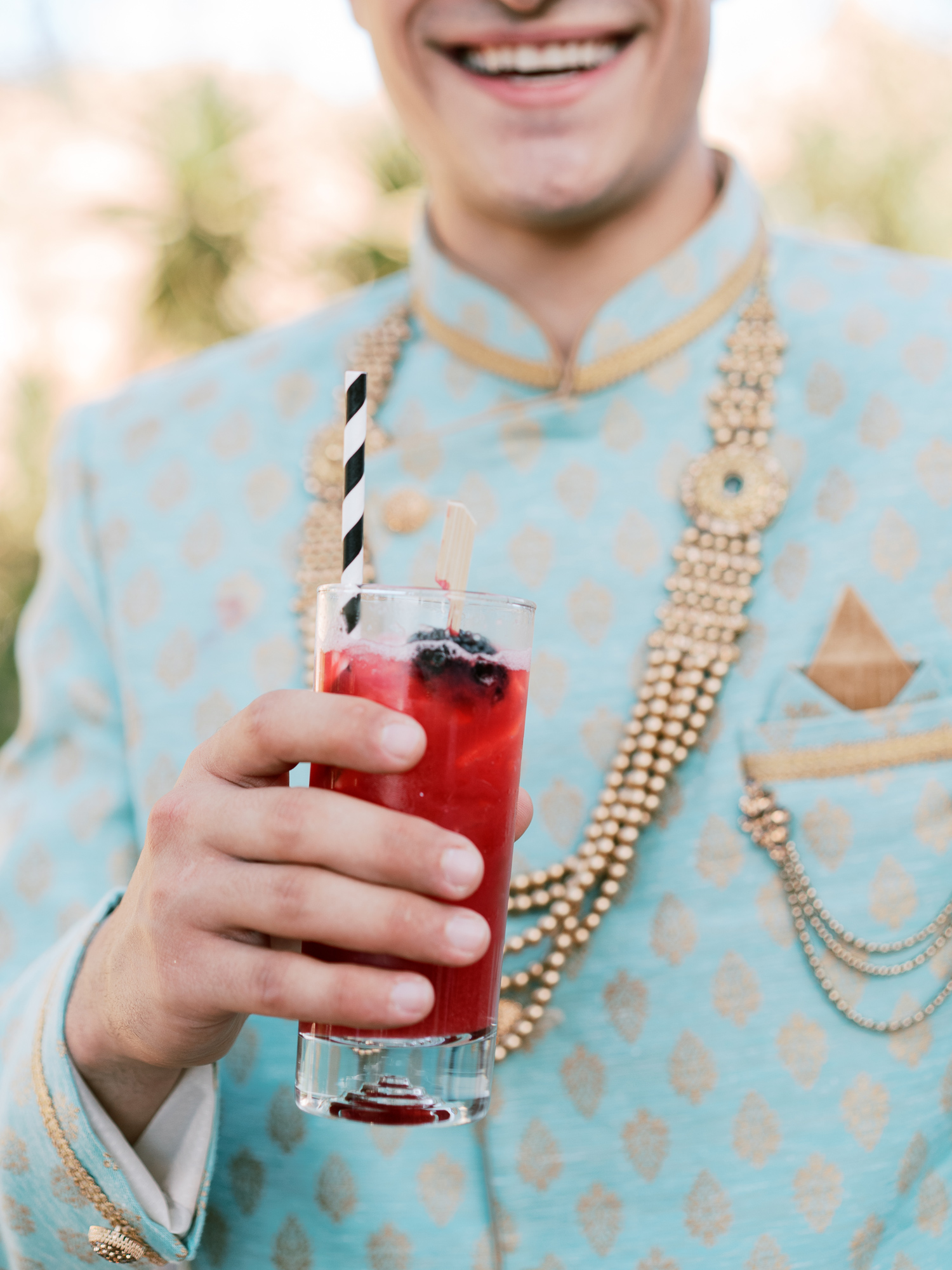 close-up of groomsman holding cocktail