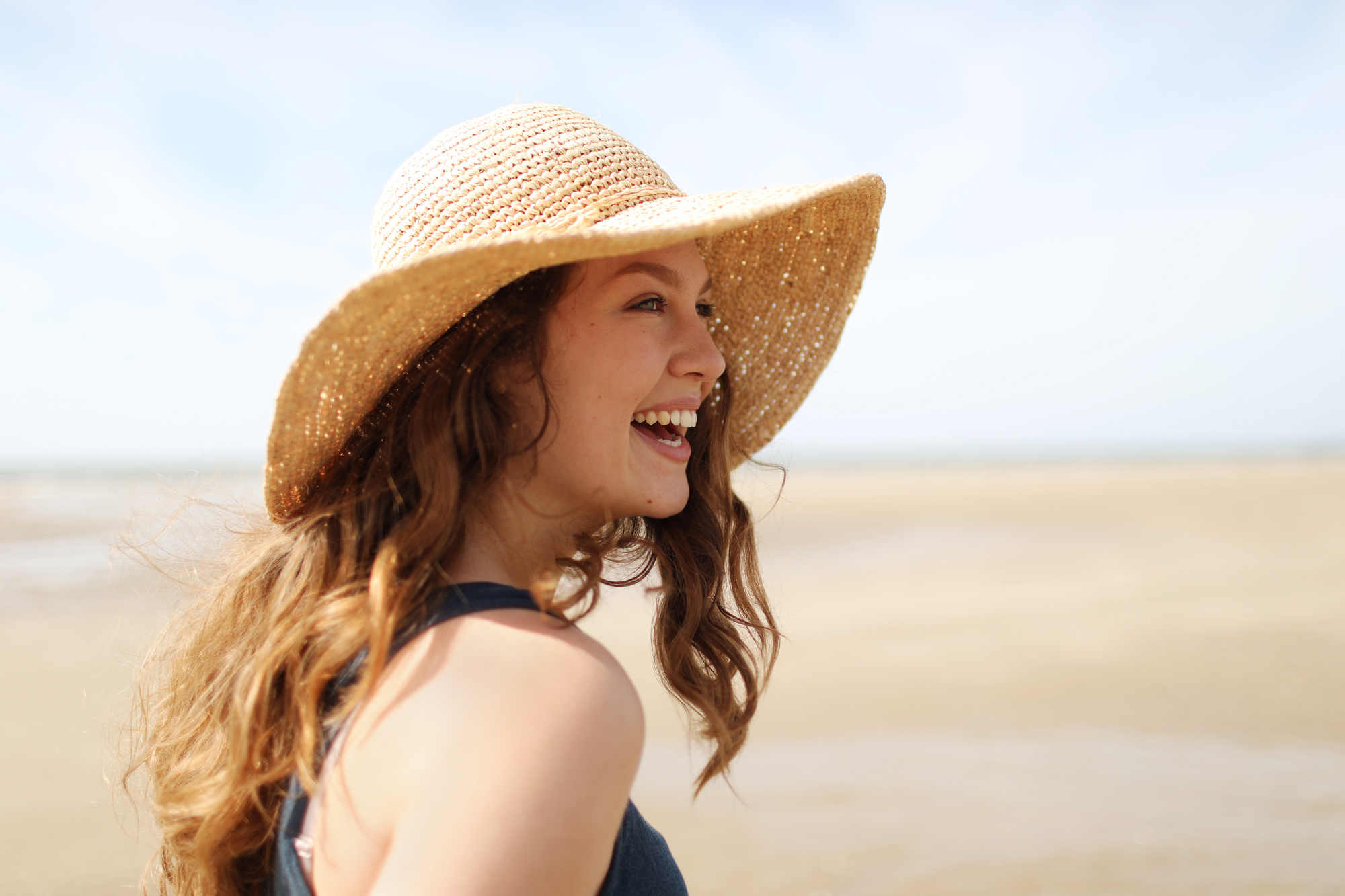 woman outdoors smiling in sun hat