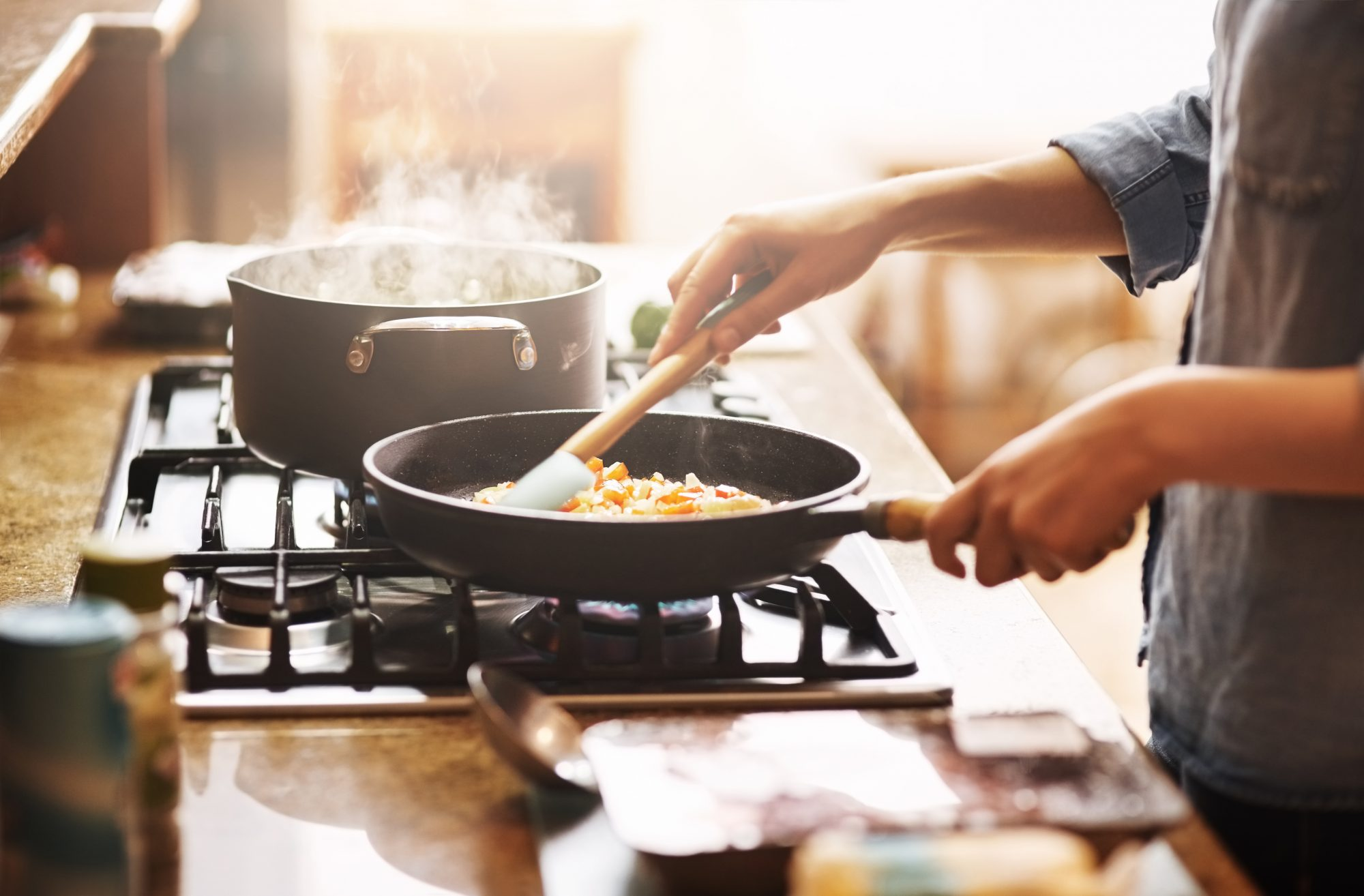 woman cooking meal on stove