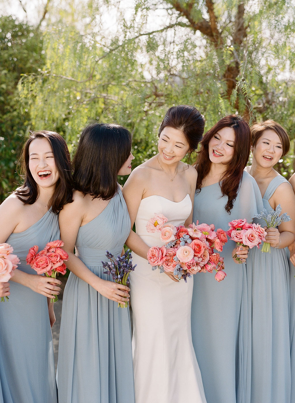 bridesmaids in slate blue holding pink and lavender bouquets with bride