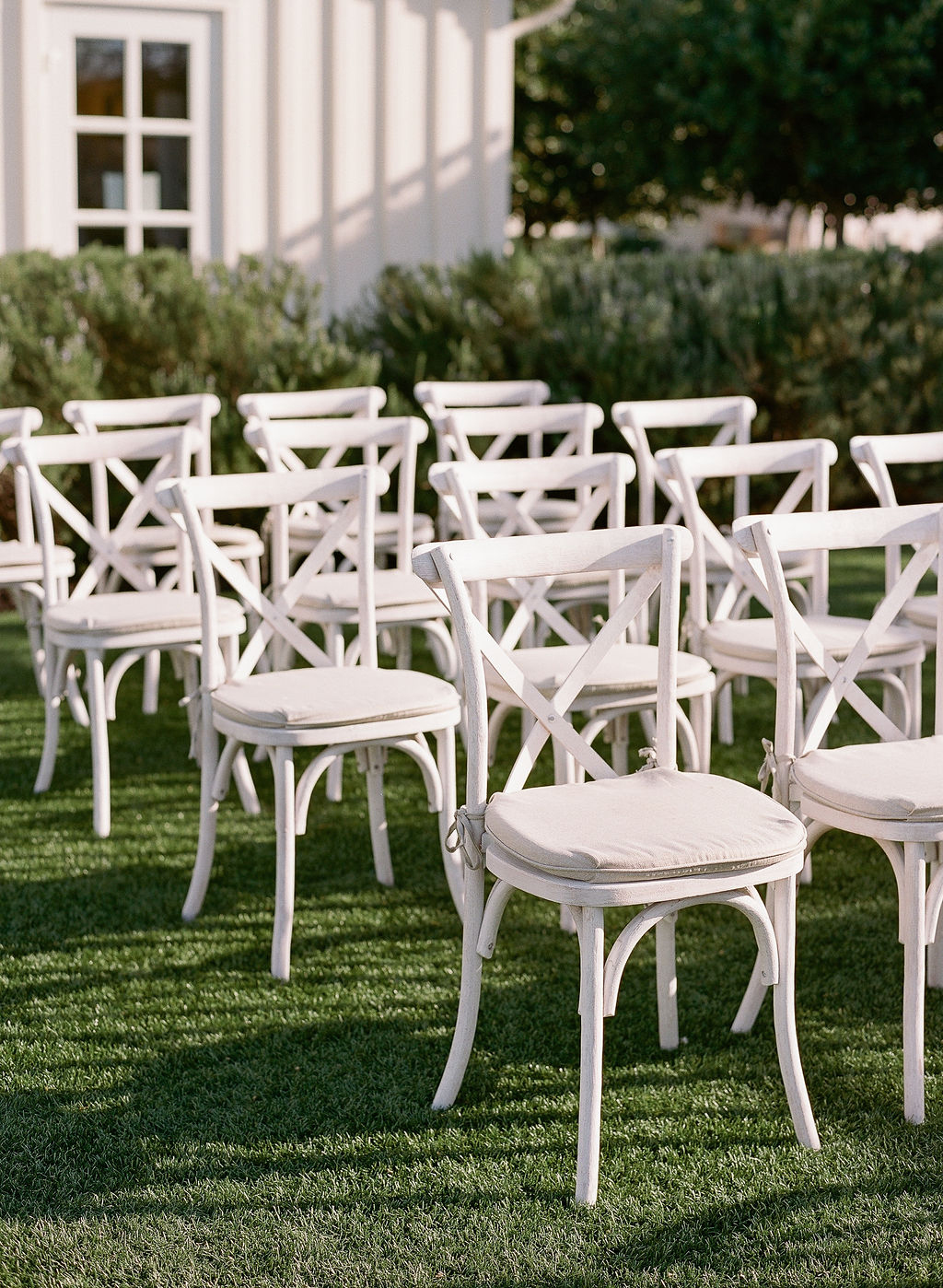white ceremony chairs with cushions set up on lawn