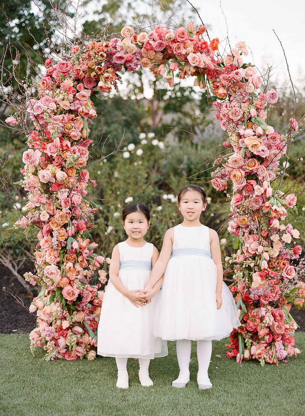 flower girls in white and blue in front of floral ceremony arch