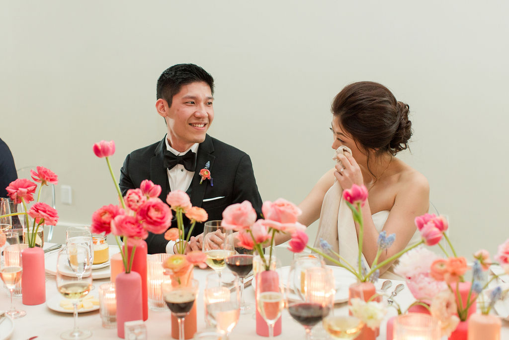 couple happy during wedding toasts at head table with flowers