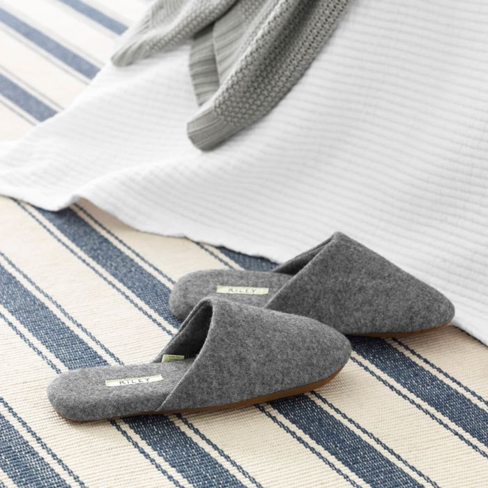gray house slippers on striped carpet