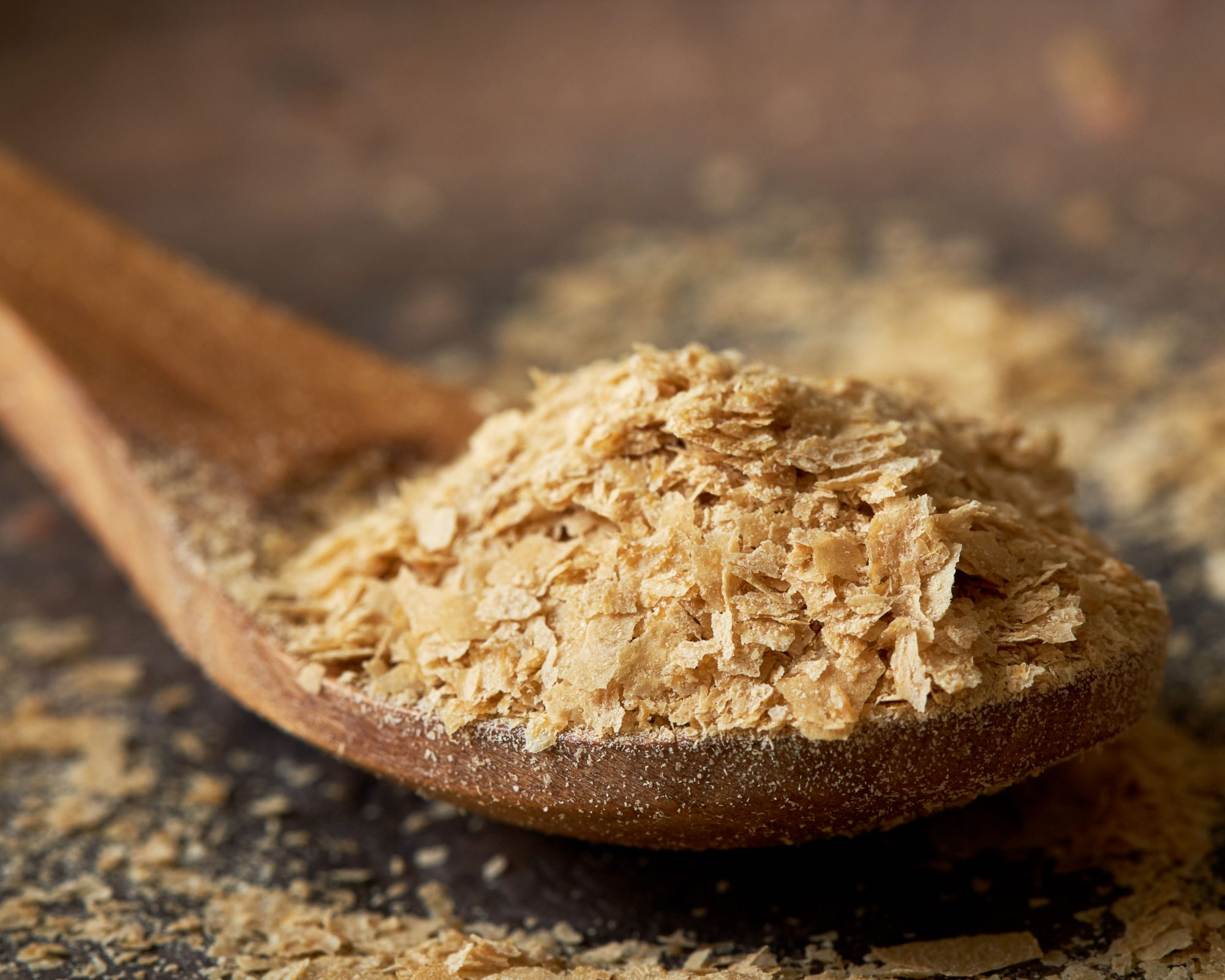 nutritional yeast flakes on wooden spoon