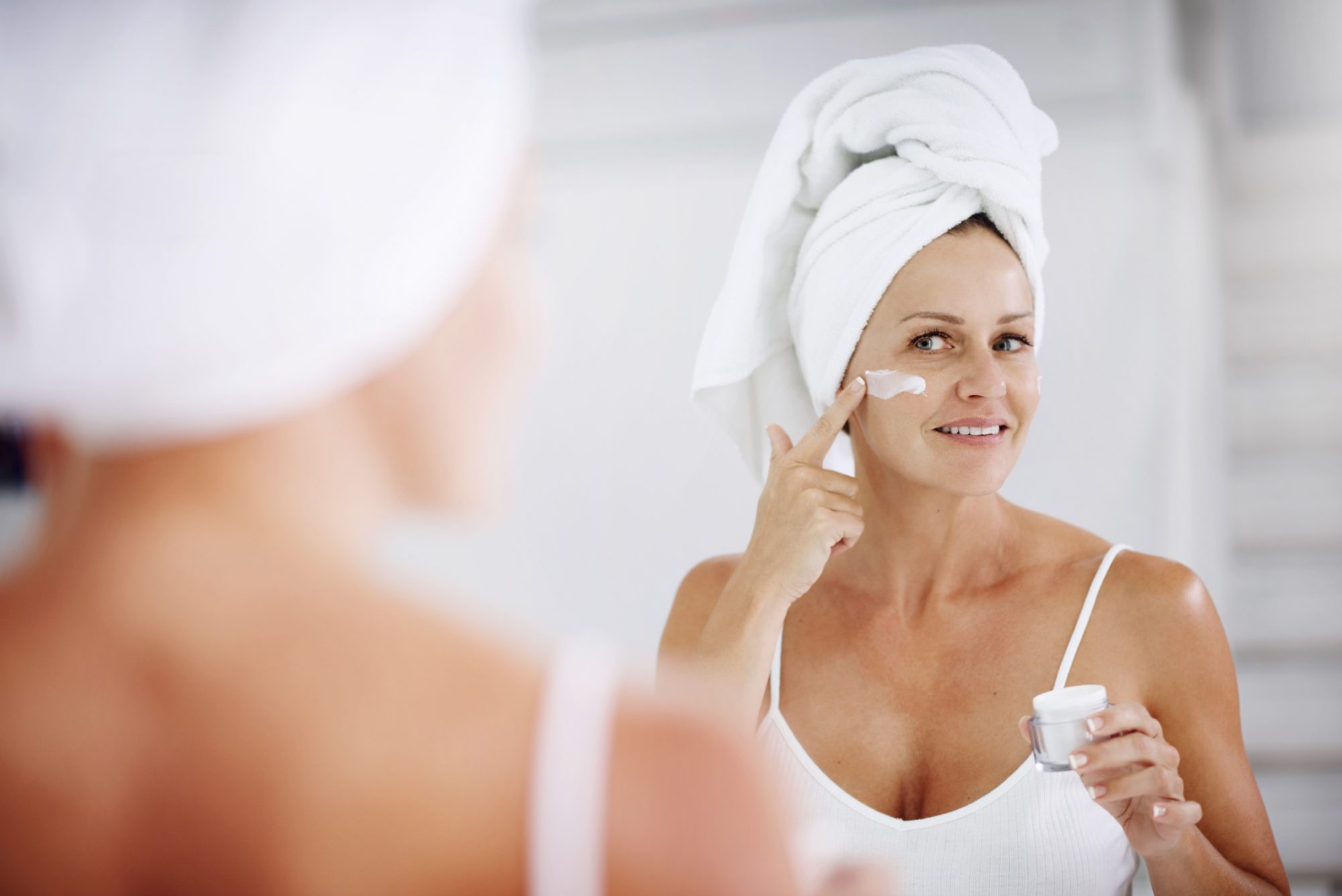 person with towel on head applying face cream