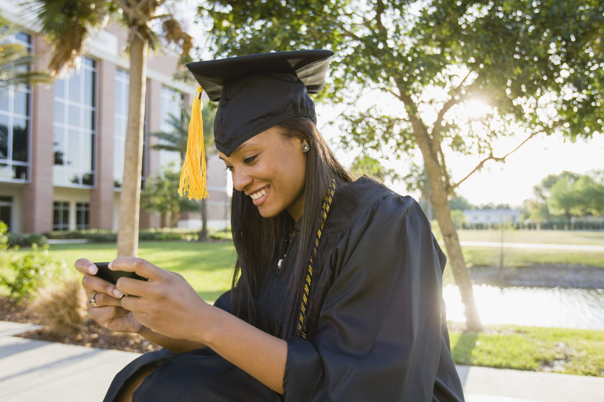 college graduate texting on a smart phone