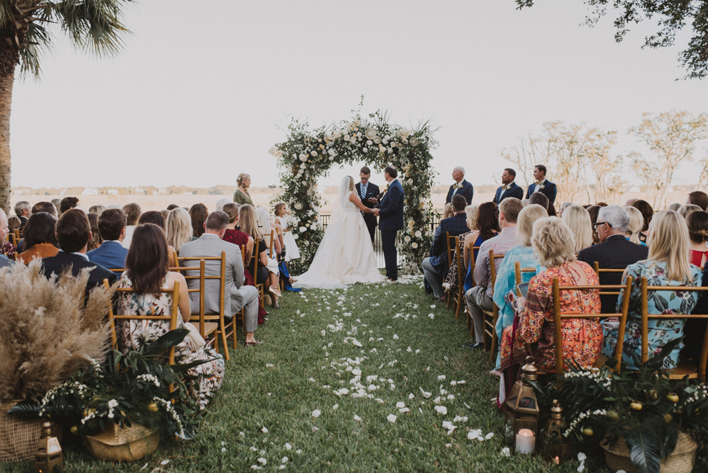 outdoor wedding ceremony with white rose petals lining aisle