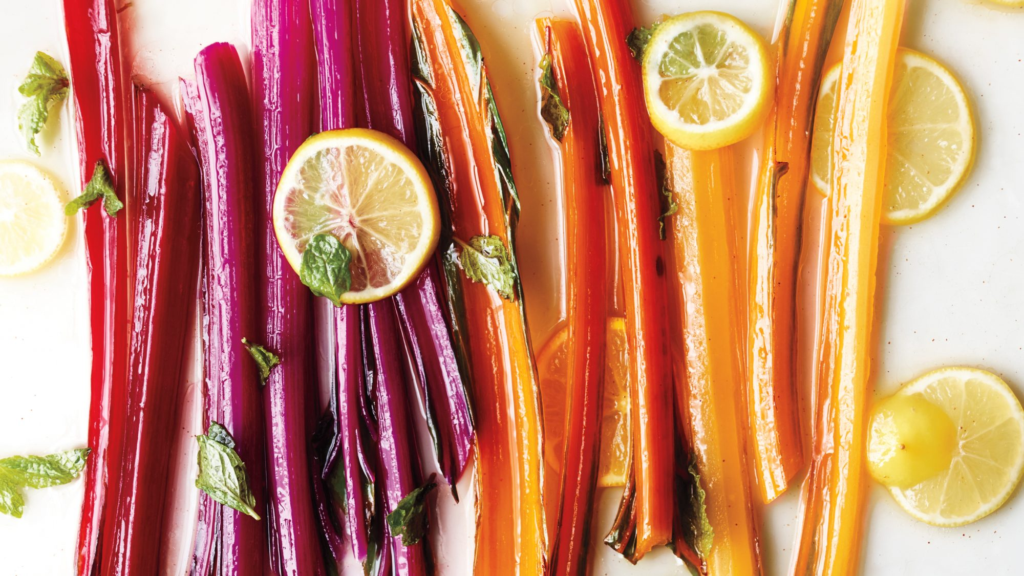 cooked Swiss chard stems in rainbow colors with lemon slices
