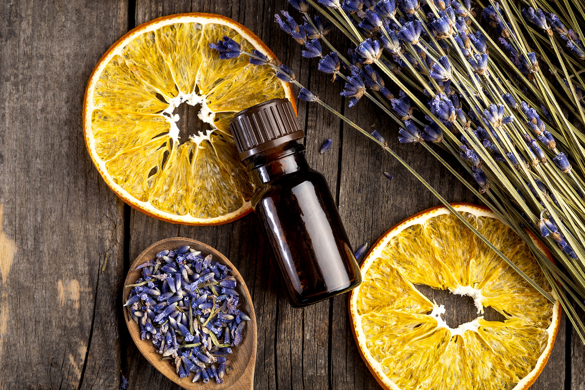 Essential oil bottle with orange slices and lavendar