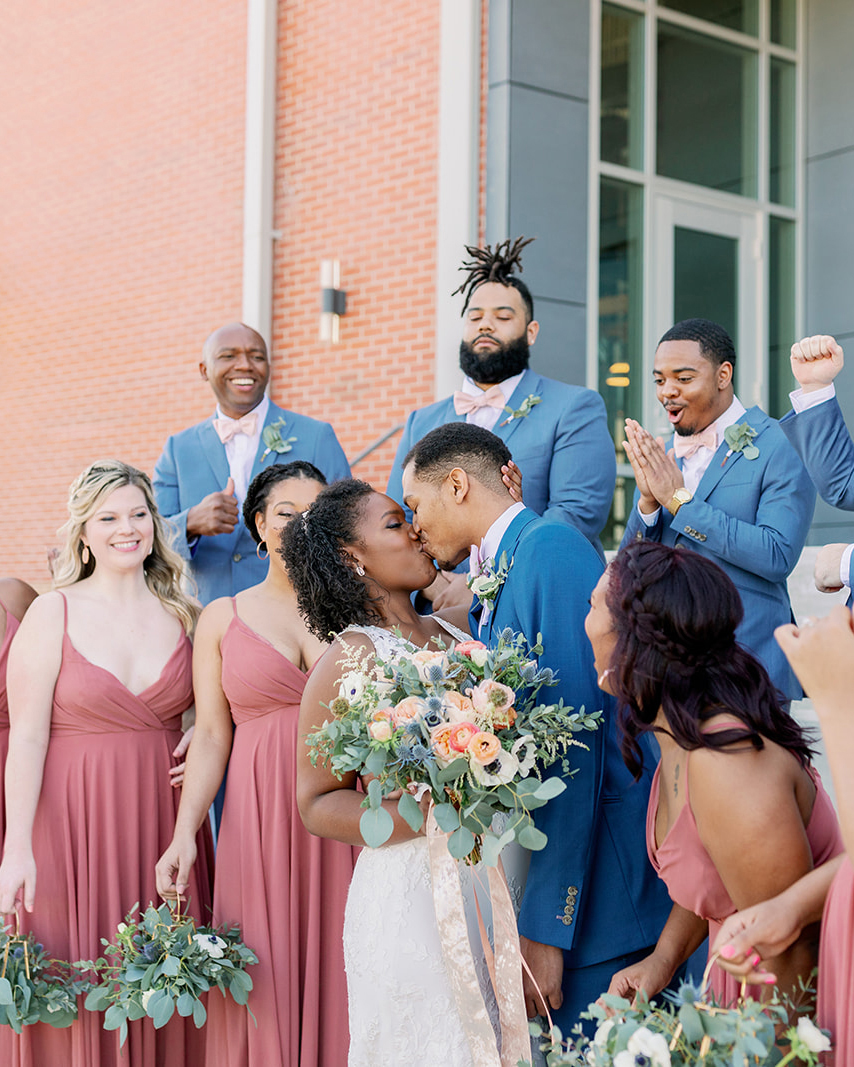 couple kiss during portraits with wedding party