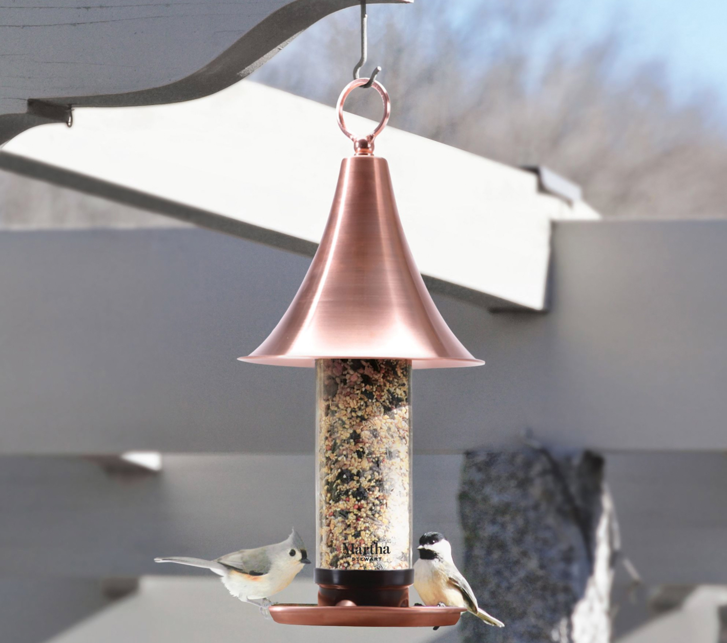 two birds eating from copper bird feeder