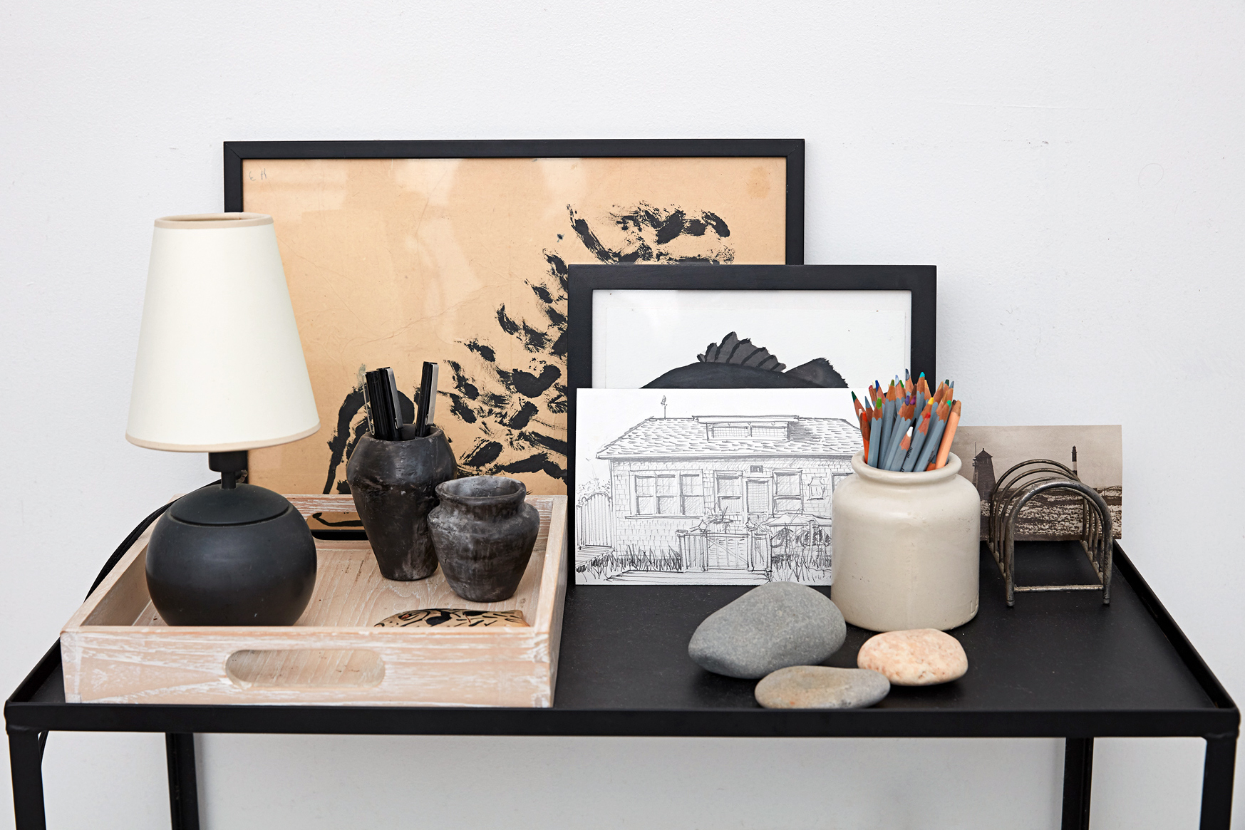 black table displaying pottery artwork and stones
