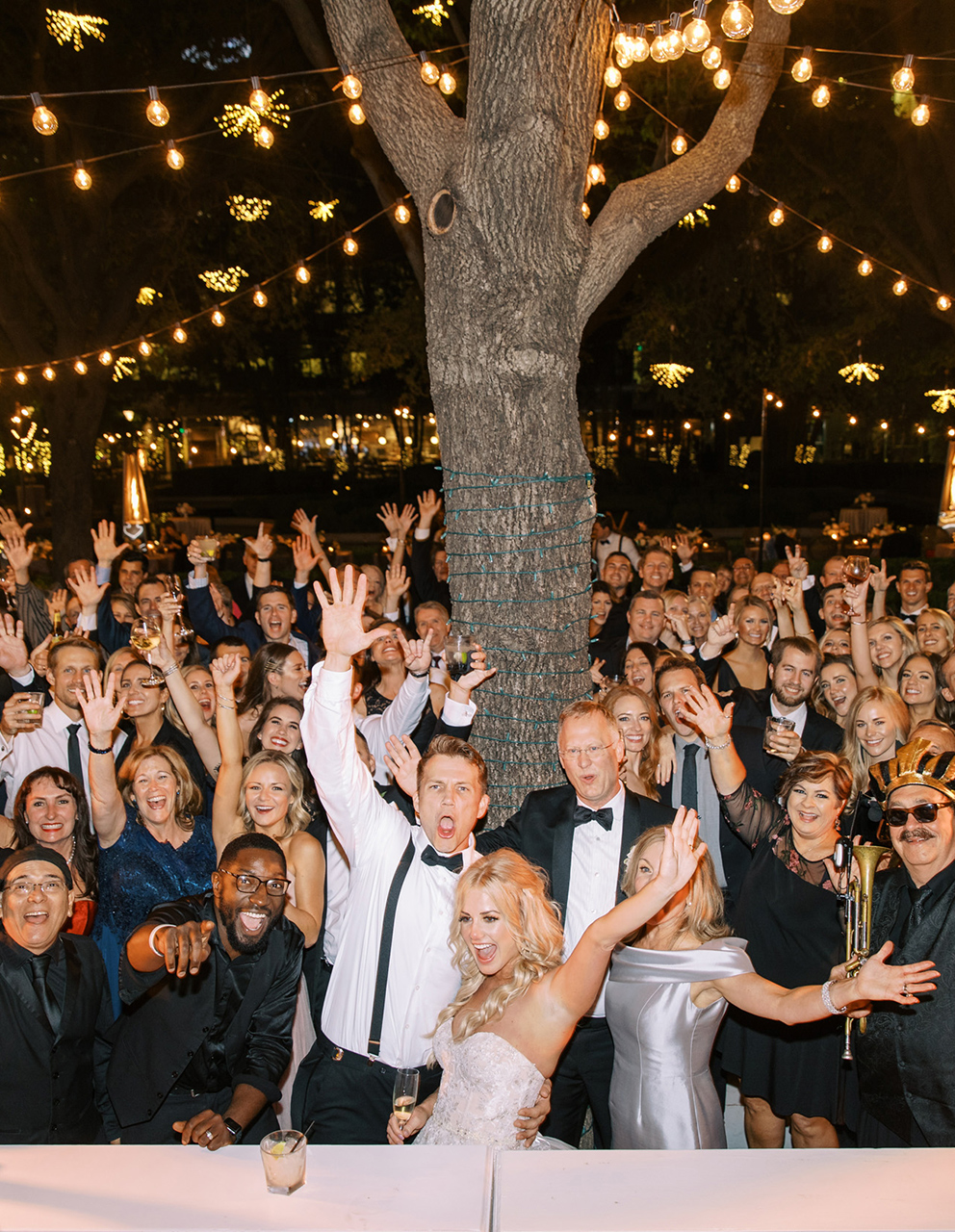 bride groom pose with guests night lighting