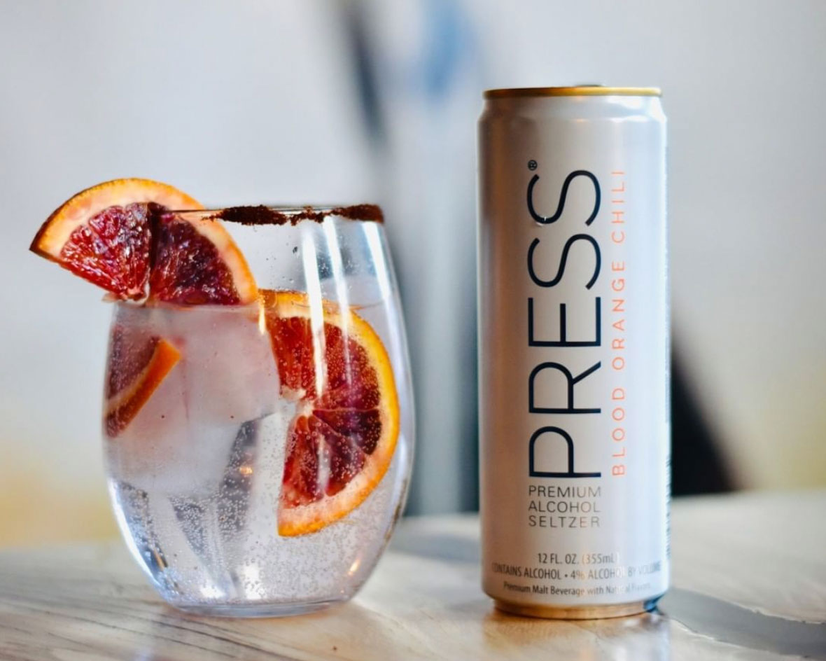 Glass with blood orange slices and seltzer and can of Press hard seltzer