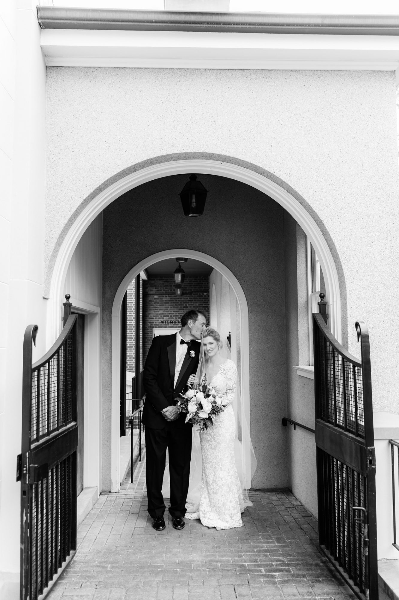 black and white photo father kissing bride's head