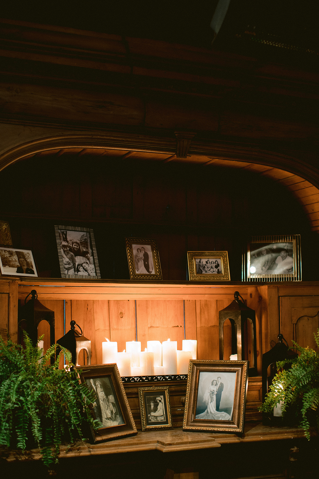 framed photos of family members lit by candles at rehearsal dinner